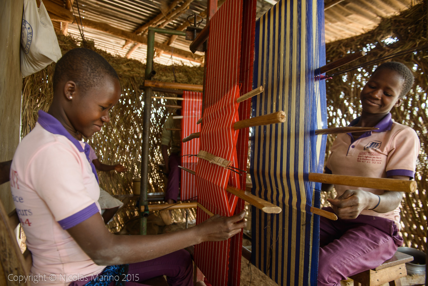 GIrls and women working on their looms in a village of northern Benin.
