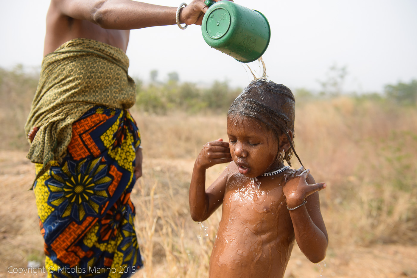 Fulani mother bathing her two daughters. Northern Togo
