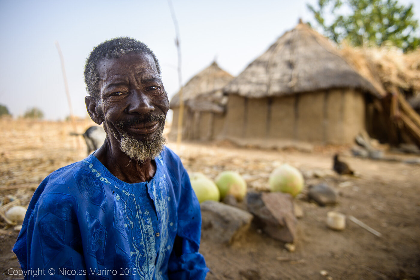 A Burkinabe man in his village, cutting pumpkins to turn them into drinking and eating containers. Burkina Faso