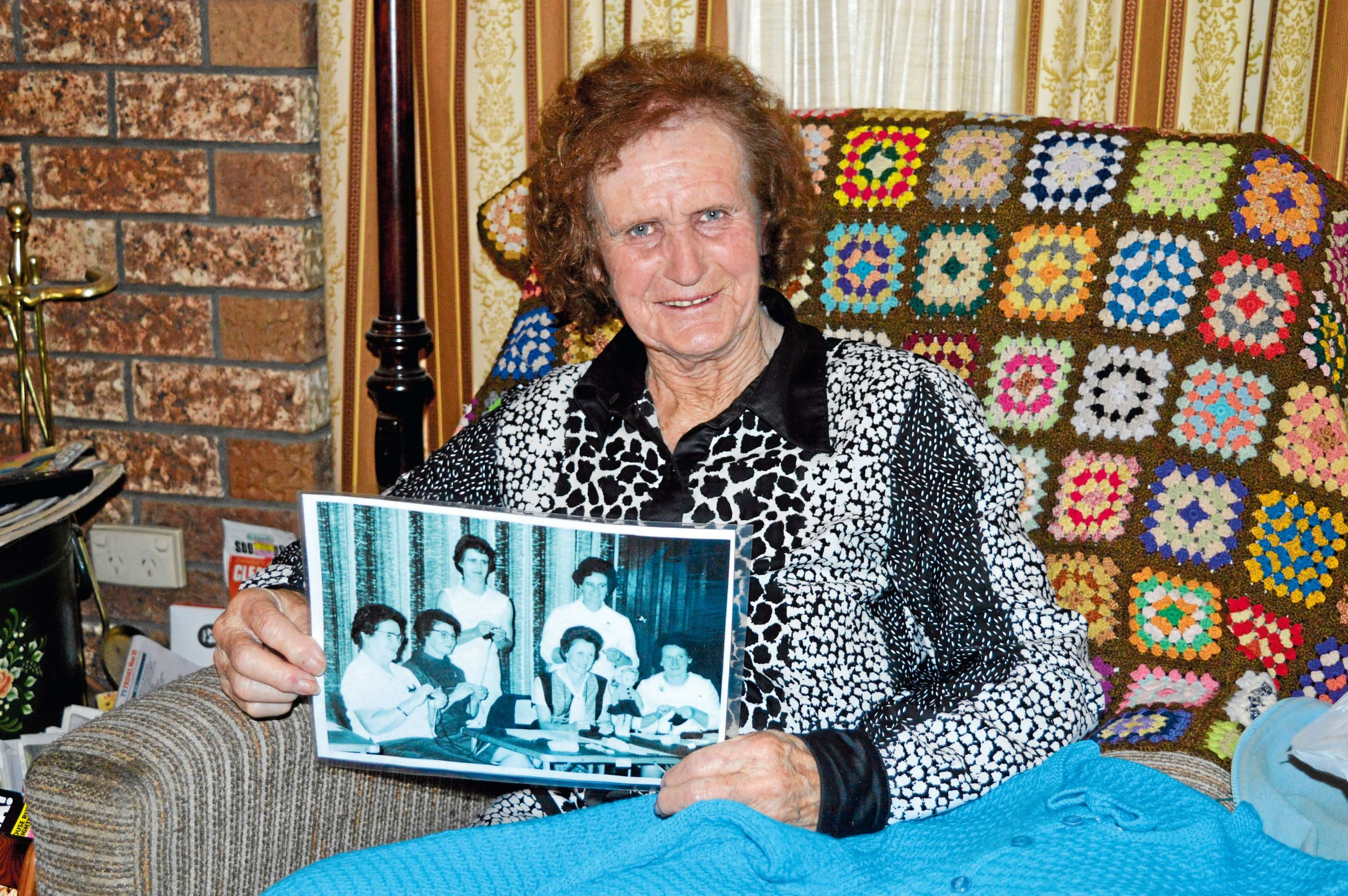 • Ringarooma resident Faye Bennett, holding a photo of her in 1968 at a knitting competition in Brisbane.
