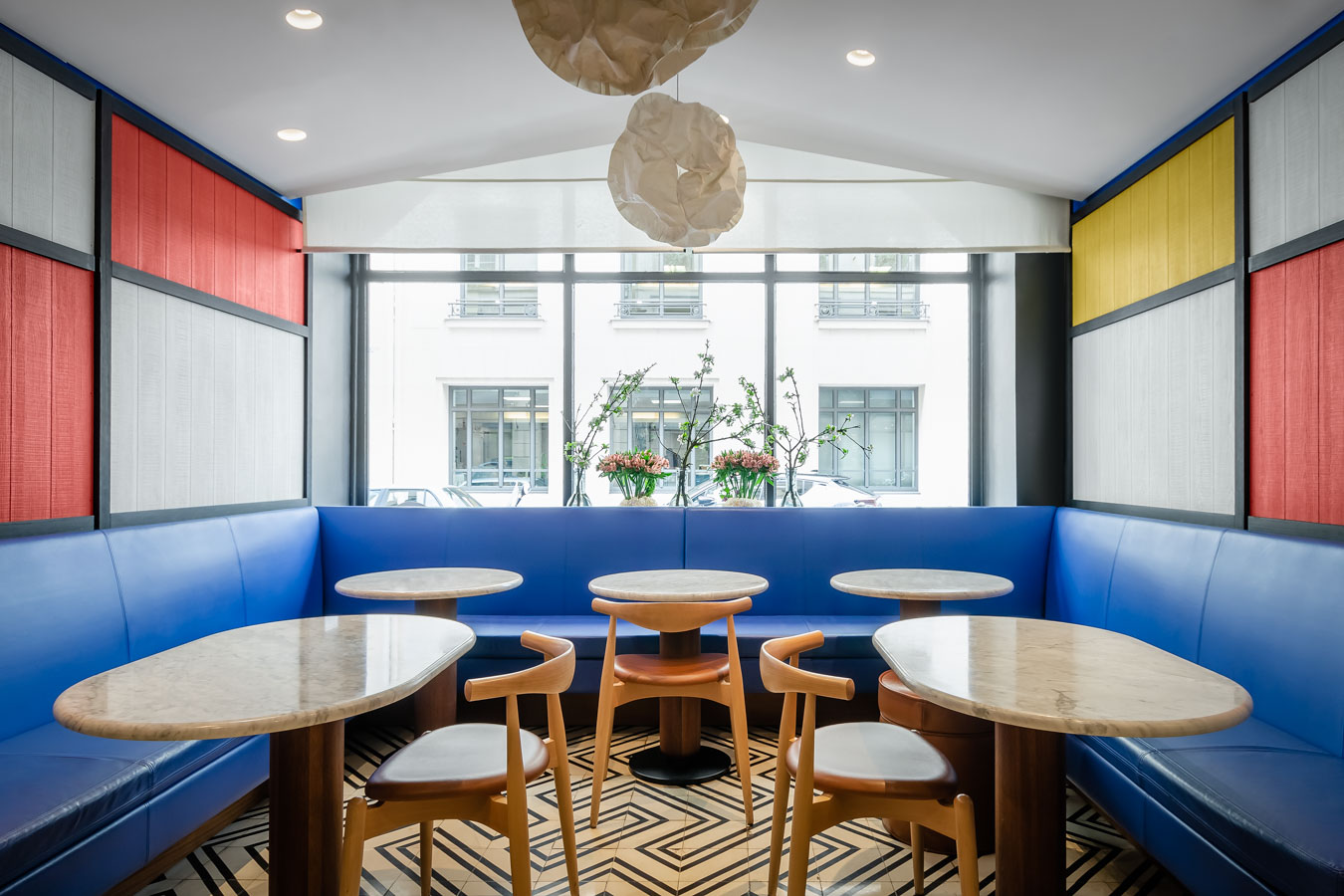 """""""Elbow Chair CH20"""", sillas diseñadas por Hans J. Werner en 1956. Las paredes están inspiradas en las pinturas neoplasticistas de Piet Mondrian. Las mesas, creadas por el estudio François Champsaur, son de diseño personalizado para el hotel con marmol de la casa Carrara. Los sillones y taburetes de cuero también son un diseño personalizado."""