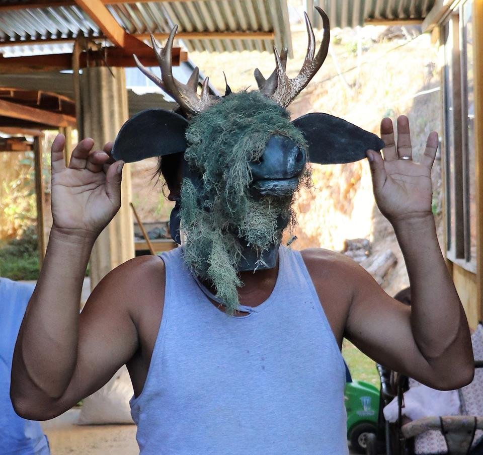 Don Ismael demonstrating the mask he wears for an annual community ceremony.