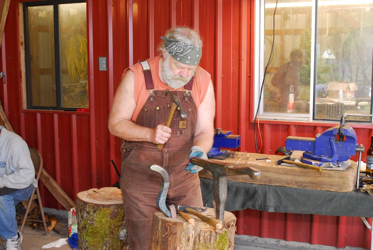 Greg Wilbur works a copper piece.