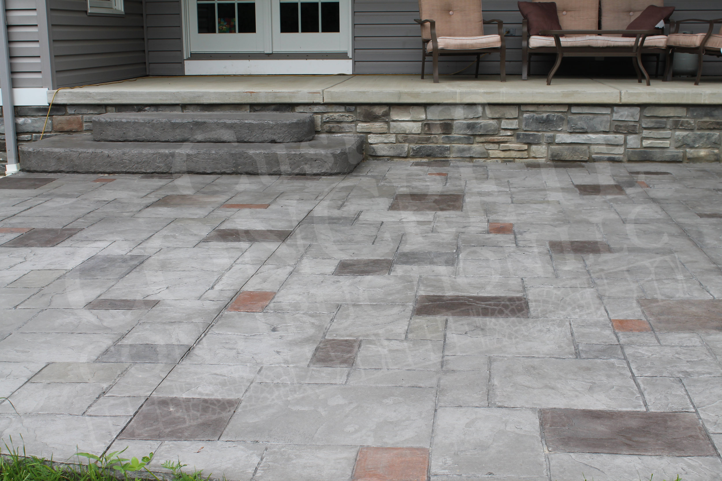 ashlar stamped patio, steps with textured rock faces, and individual hand-staining work