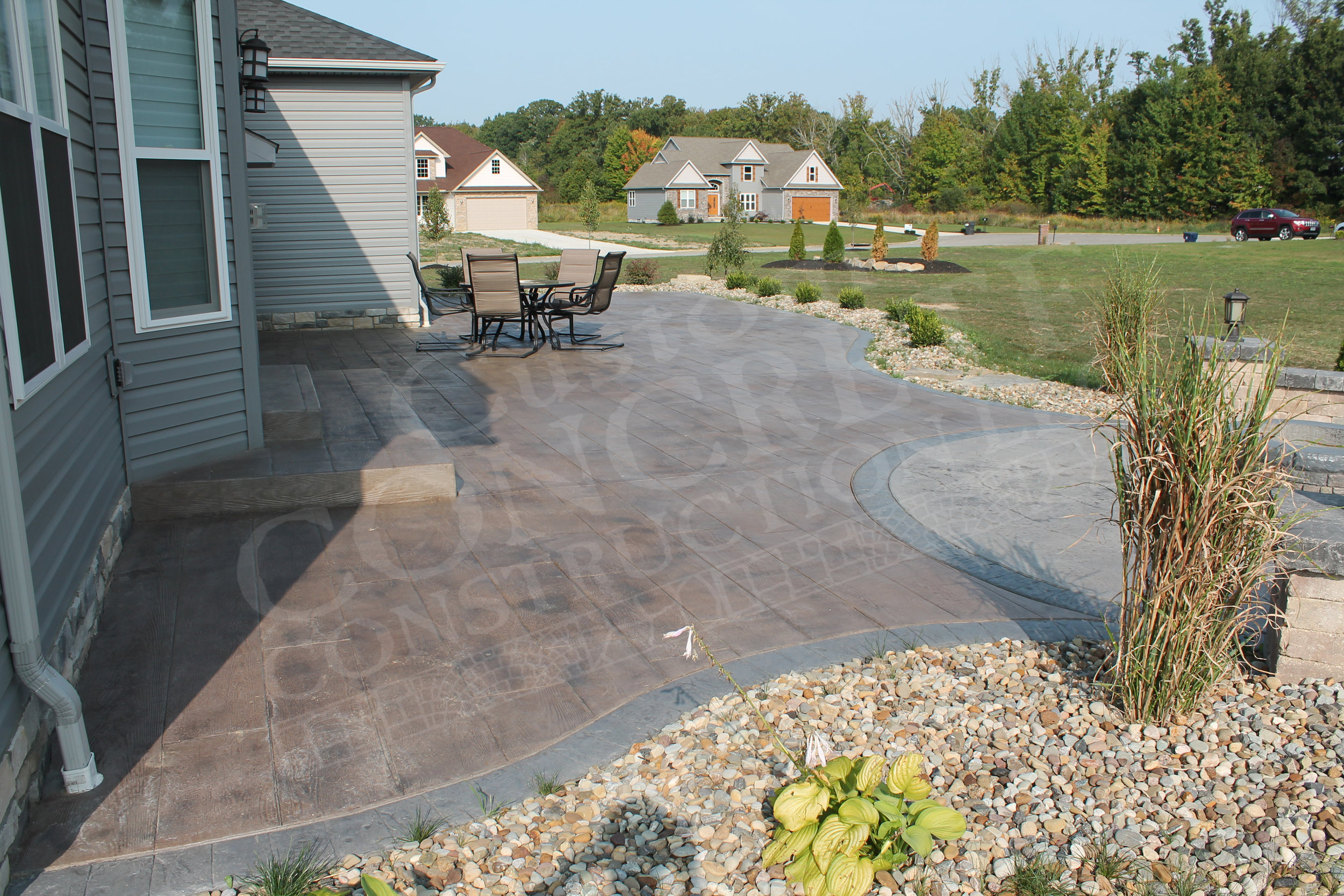 wood plank stamped patio with stamped textured fire pit area and stamped tile exterior borders