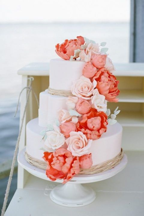 This beautiful wedding cake gives us beach vibes, its very simple yet stunning. While the main part of the cake is white and plain, it lets us fix our eyes on coral flowers that give that POP of colour.  https://www.pinterest.ca/pin/555842779005783452/