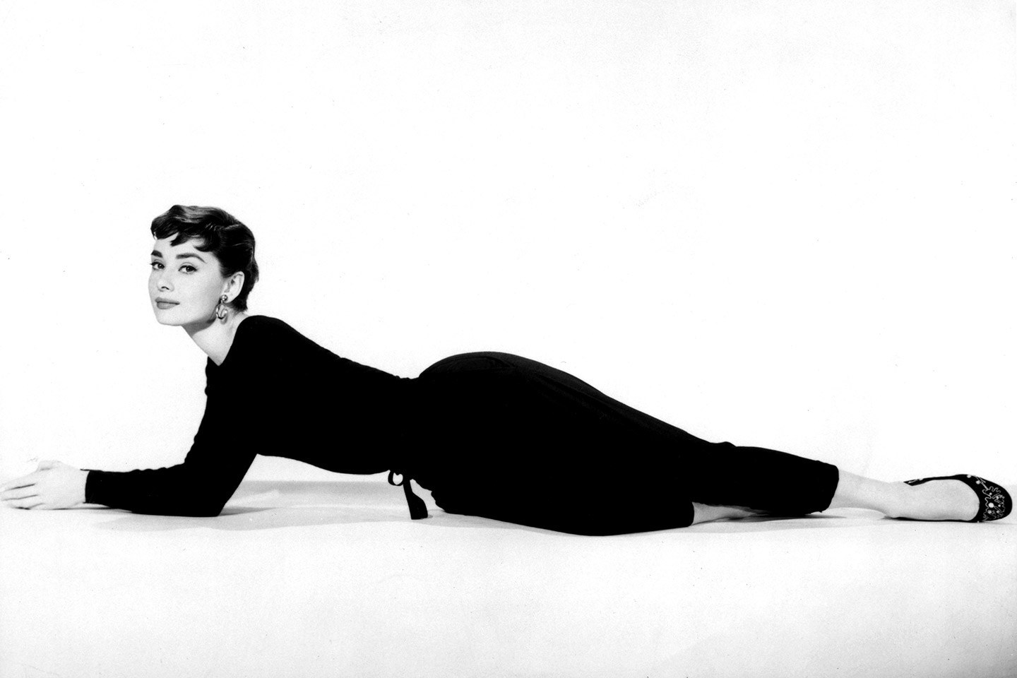 """Photo Credit: Moviepix / Getty Images   very week,VF.com staffers pick an iconic photograph and examine what really went on behind the shot. Today, we look at a 1954 photograph of Audrey Hepburn that furthered her role as an international style star and forged a lifelong friendship with a major French designer.   Before the diamonds and pearls of Breakfast at Tiffany's, there was the quietly seductive black pantsuit in  Sabrina . With a cinched waist and embellished flats, starlet Audrey Hepburn took a simple promotional film photo and made it one of the most talked about outfits of 1954.  Photographed by Bud Fraker, former department head of still photography at Paramount Pictures, Hepburn lounged with a knowing smile—although she probably couldn't predict the universal acclaim and Academy Award nomination her performance in Sabrina would gain.  The design lines are blurry as to who originally created the black pantsuit. The idea probably stemmed from a combination of the legendary head of the studio's wardrobe department, Edith Head, and the then-young-designer  Hubert de Givenchy, whose French fashion house was founded two years prior. Over multiple fittings, a friendship between Hepburn and Givenchy blossomed.  """"Little by little, our friendship grew and with it a confidence in each other,"""" Givenchy  told the  Telegraph.    Much to Hepburn's chagrin, Givenchy never got the recognition he deserved for his Sabrina creations: """"[Sabrina] won an Oscar for the dresses but I didn't get any credit,"""" Givenchy said to the  The Wall Street Journal.  """"She was furious. She demanded 'Each time I'm in a film, Givenchy dresses me.'""""  After working together for several more movies, including  Funny Face, Breakfast at Tiffany's , and  How to Steal a Million , they began to consider each other not just friends, but family. Hepburn referred to him as her big brother, and Givenchy said that their relationship  was """"a kind of marriage.""""   She would call """"just to tell me how much she l"""