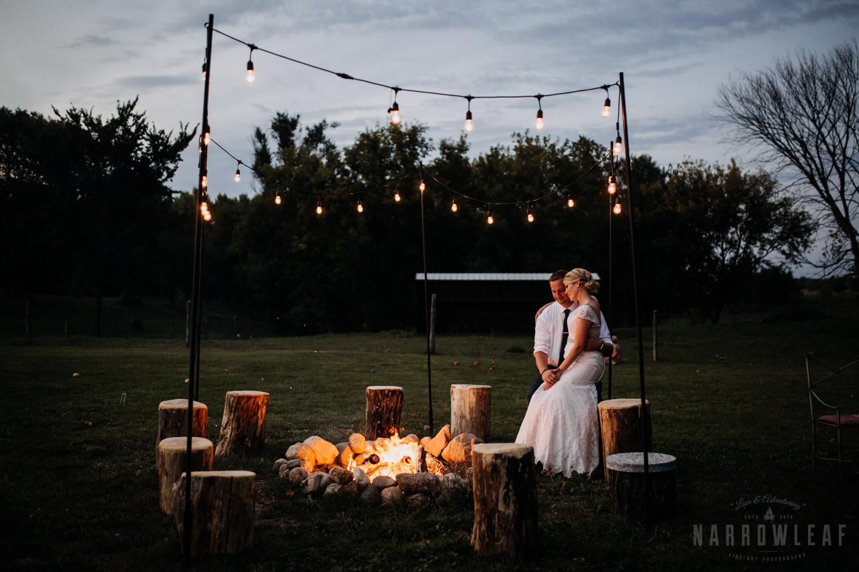 bride-groom-cuddling-by-the-bonfire-under-cafe-lights-night-33.jpg