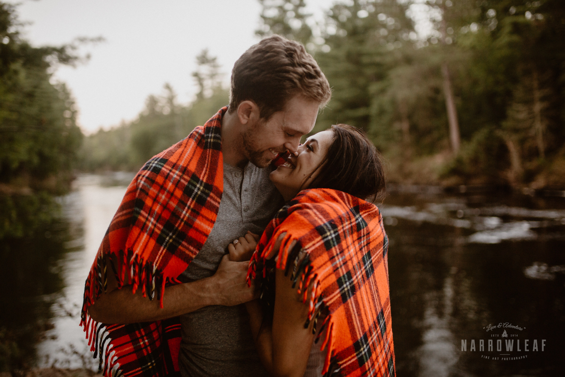Couple cuddled in a plaid blanket in Northern Minnesota