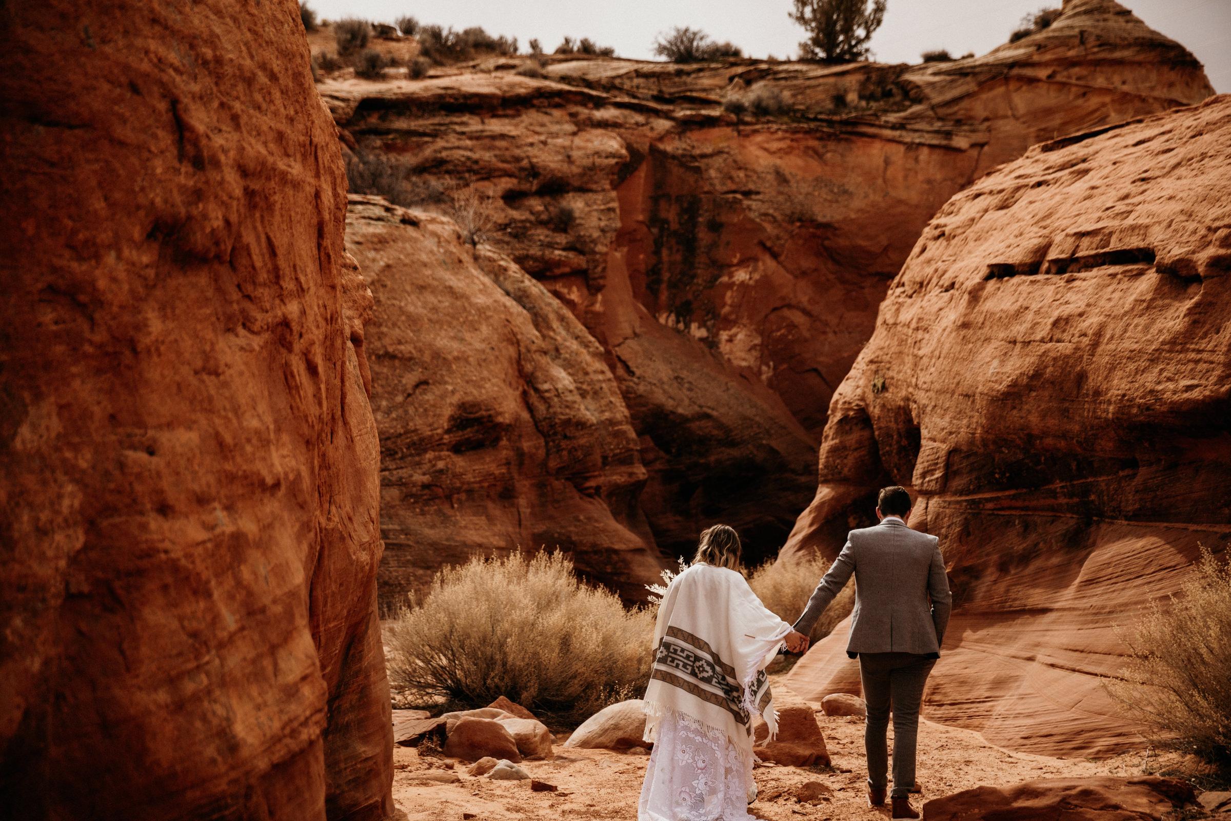 boho-elopement-couple-walking-into-page-arizona-slot-canyon.jpg