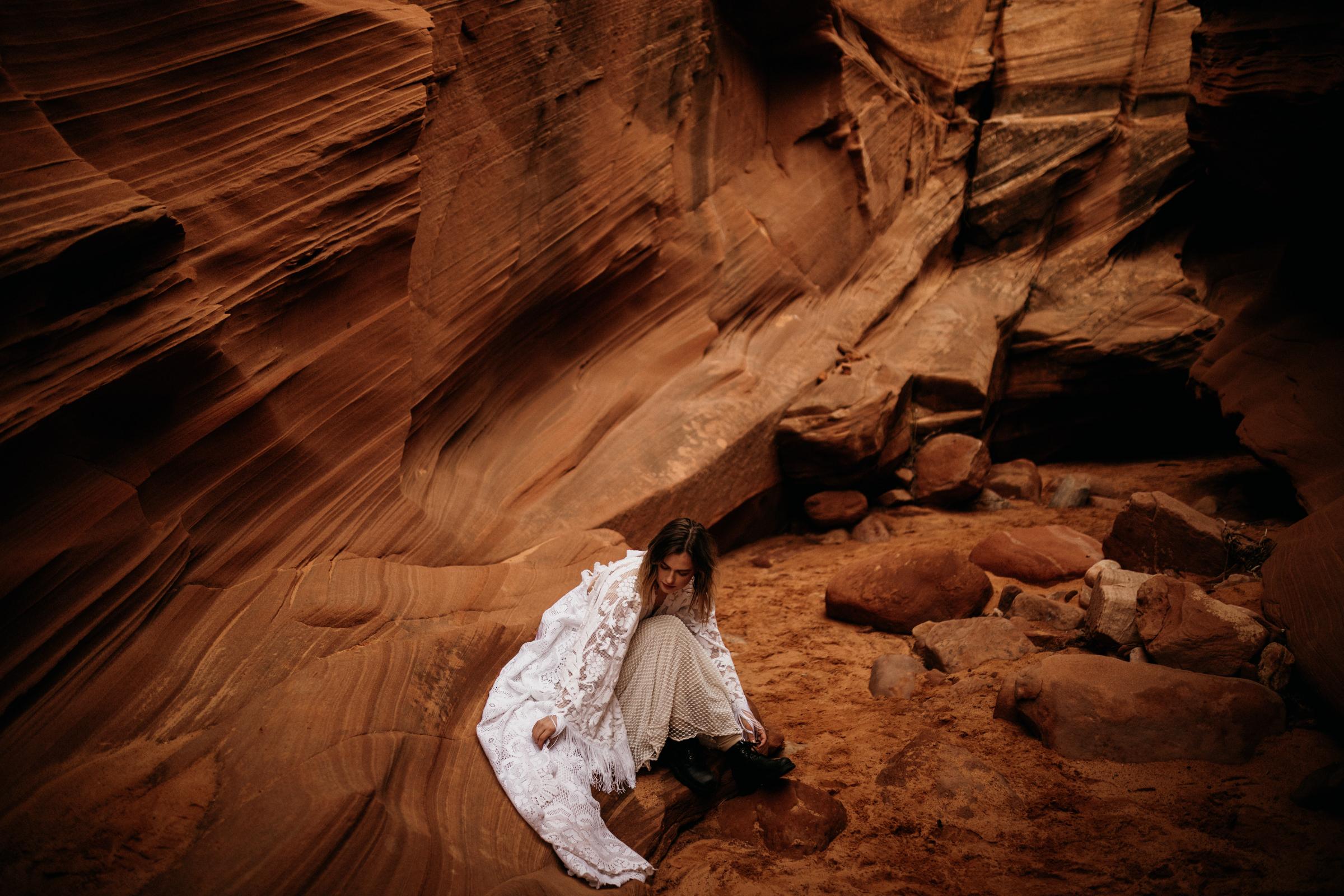 boho-bride-sitting-in-arizona-slot-canyon.jpg