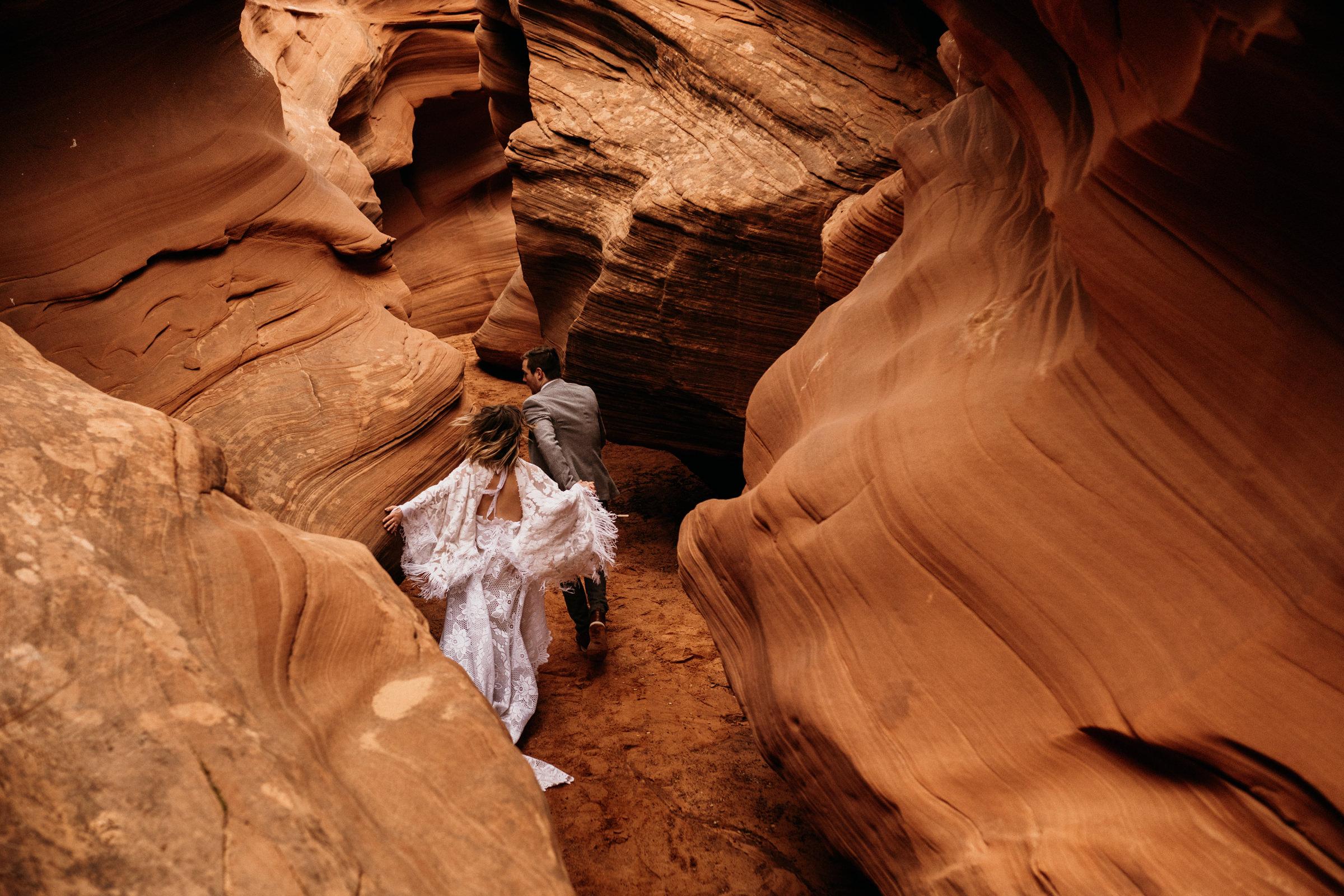 eloping-couple-running-through-slot-canyon.jpg