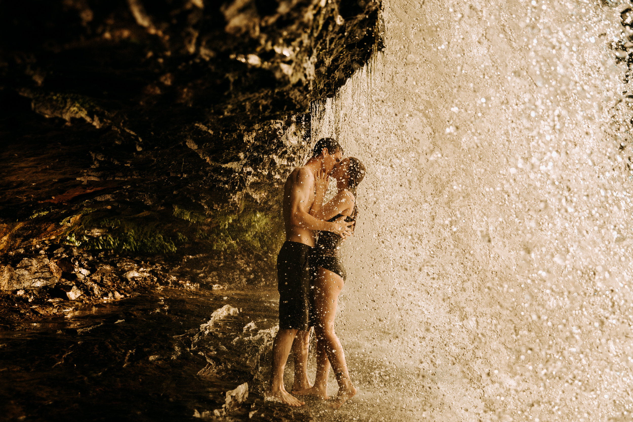 Adventure photographer captures image of a couple in kissing under a waterfall.