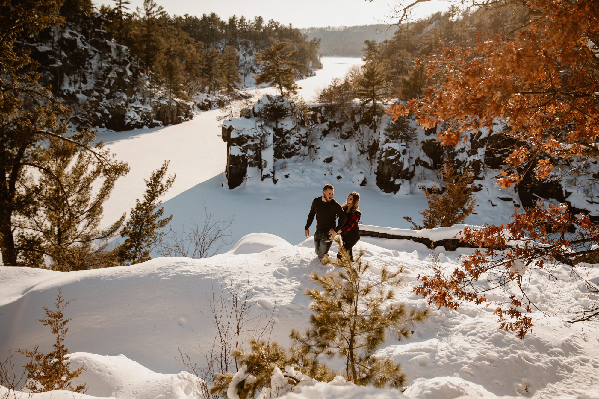 a couple hiking the epic landscape of the minnesota bluffs over the st. croix river.