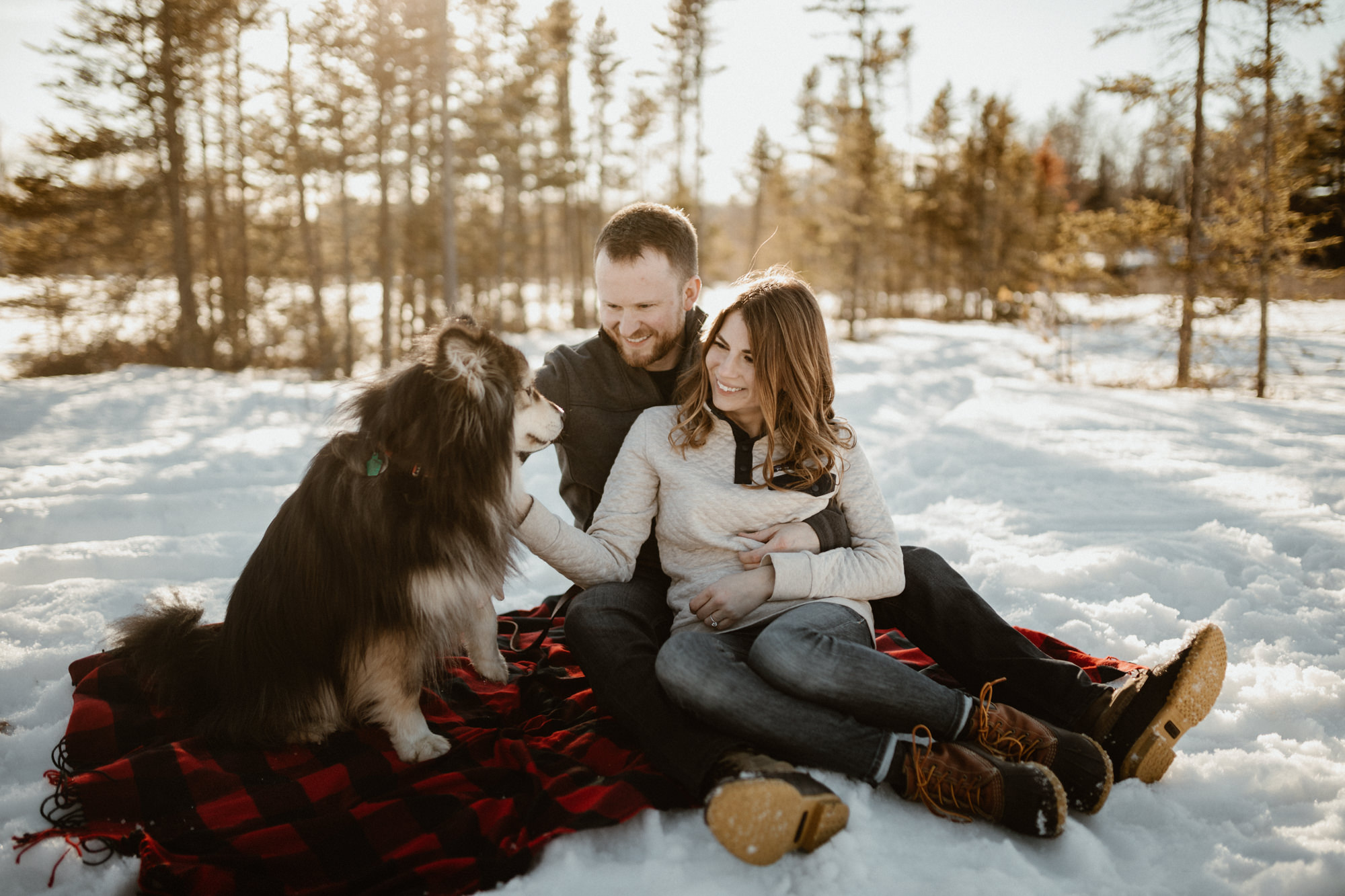 A couple and their Finnish Lapphund sitting on a plaid blanket in the snow.