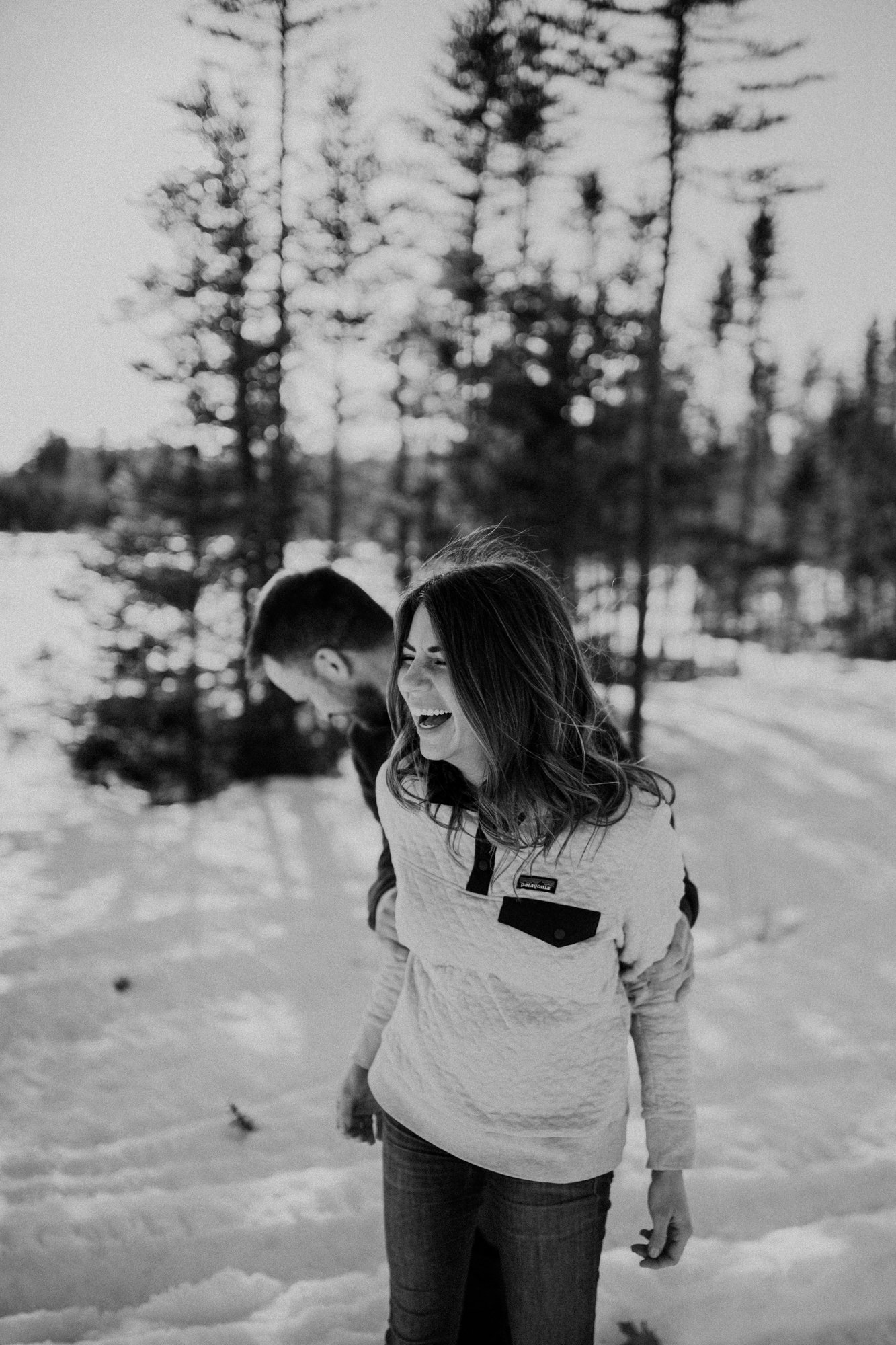 Candid moment of a couple playing in the snow during their engagement session up north.