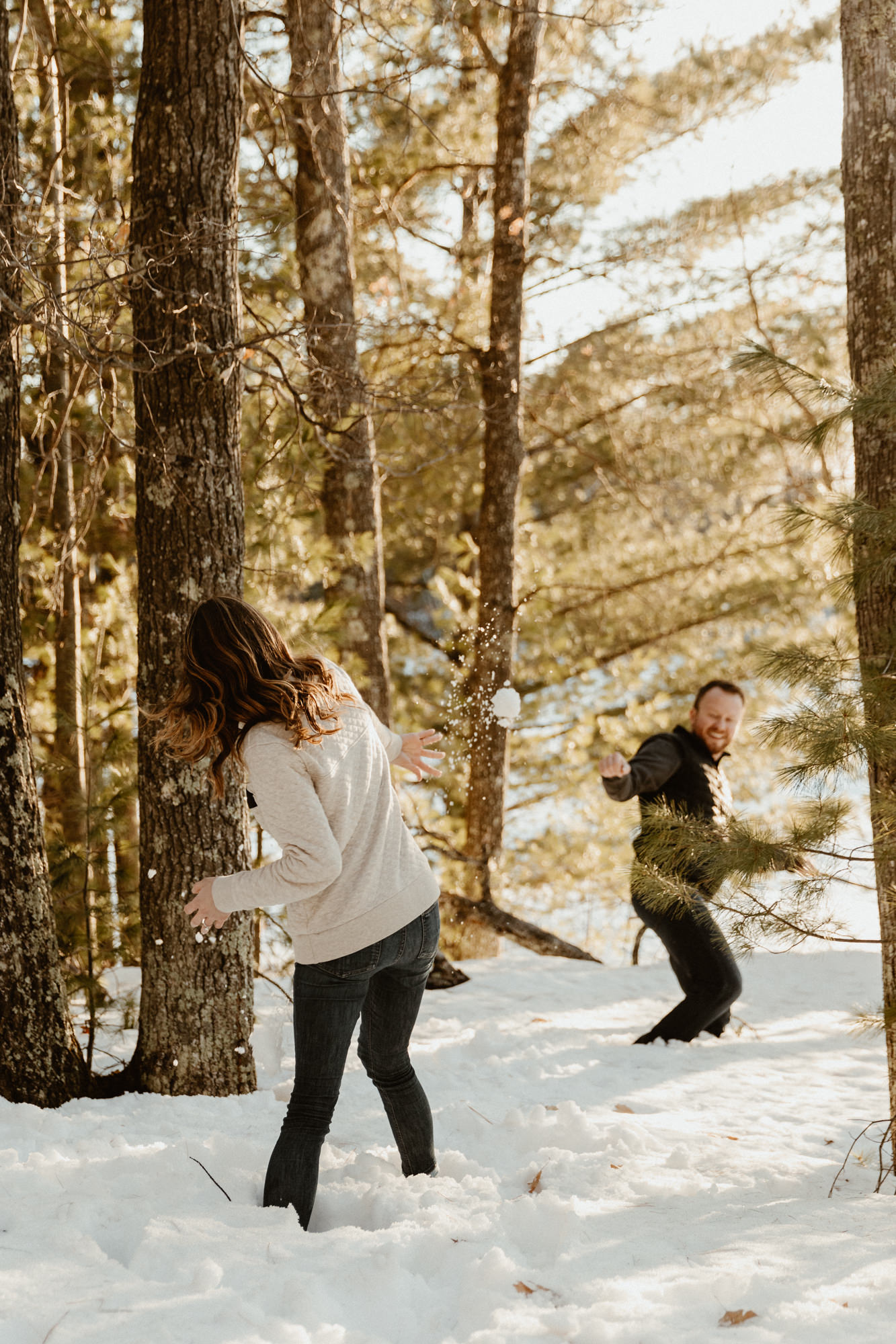 Couple having a snowball fight in the woods.