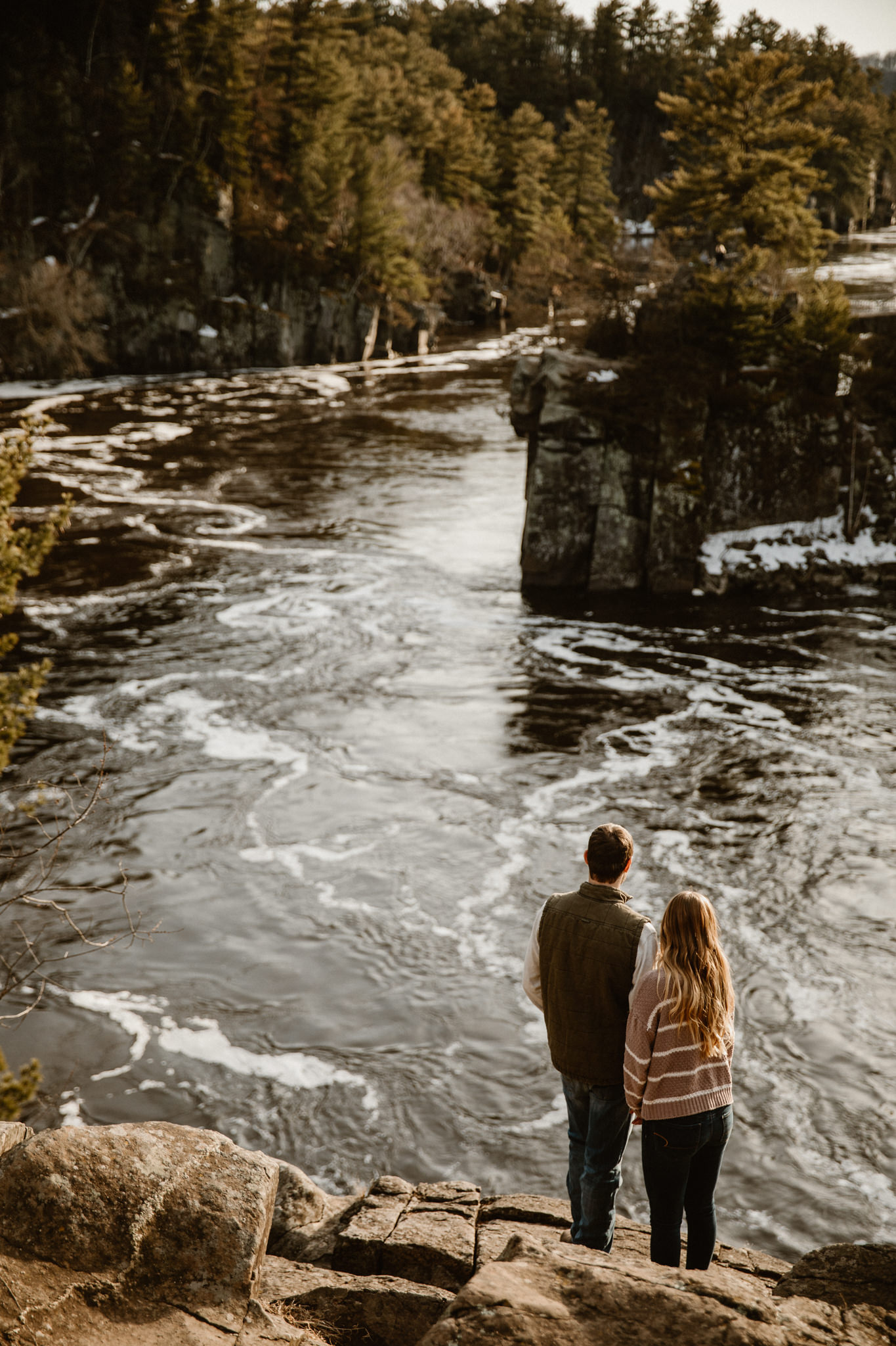Adventurous couple exploring the bluffs in Wisconsin during their adventure engagement photos.
