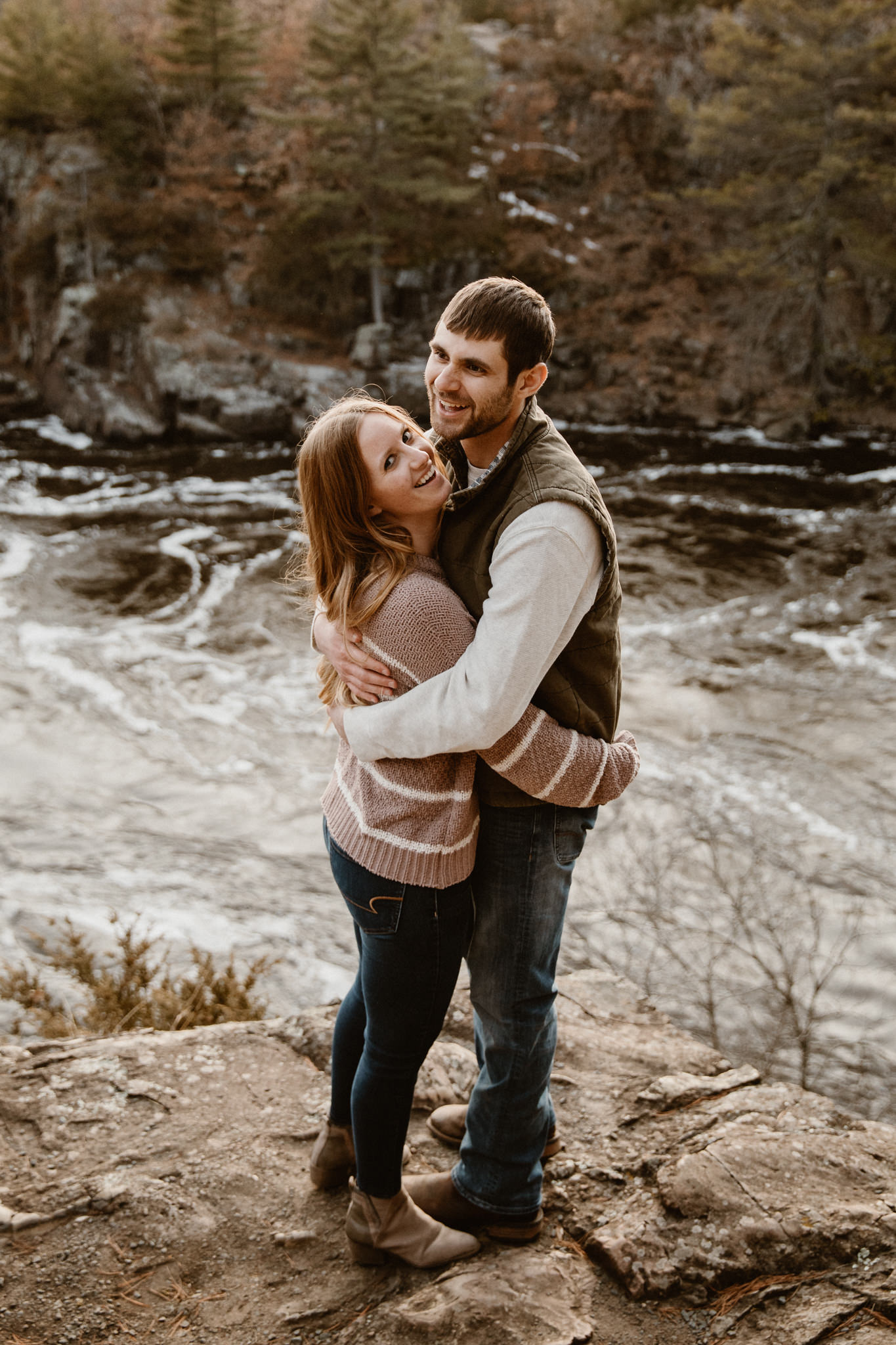 Couple laughing during their adventurous engagement photo session overlooking Taylors Falls, Minnesota.