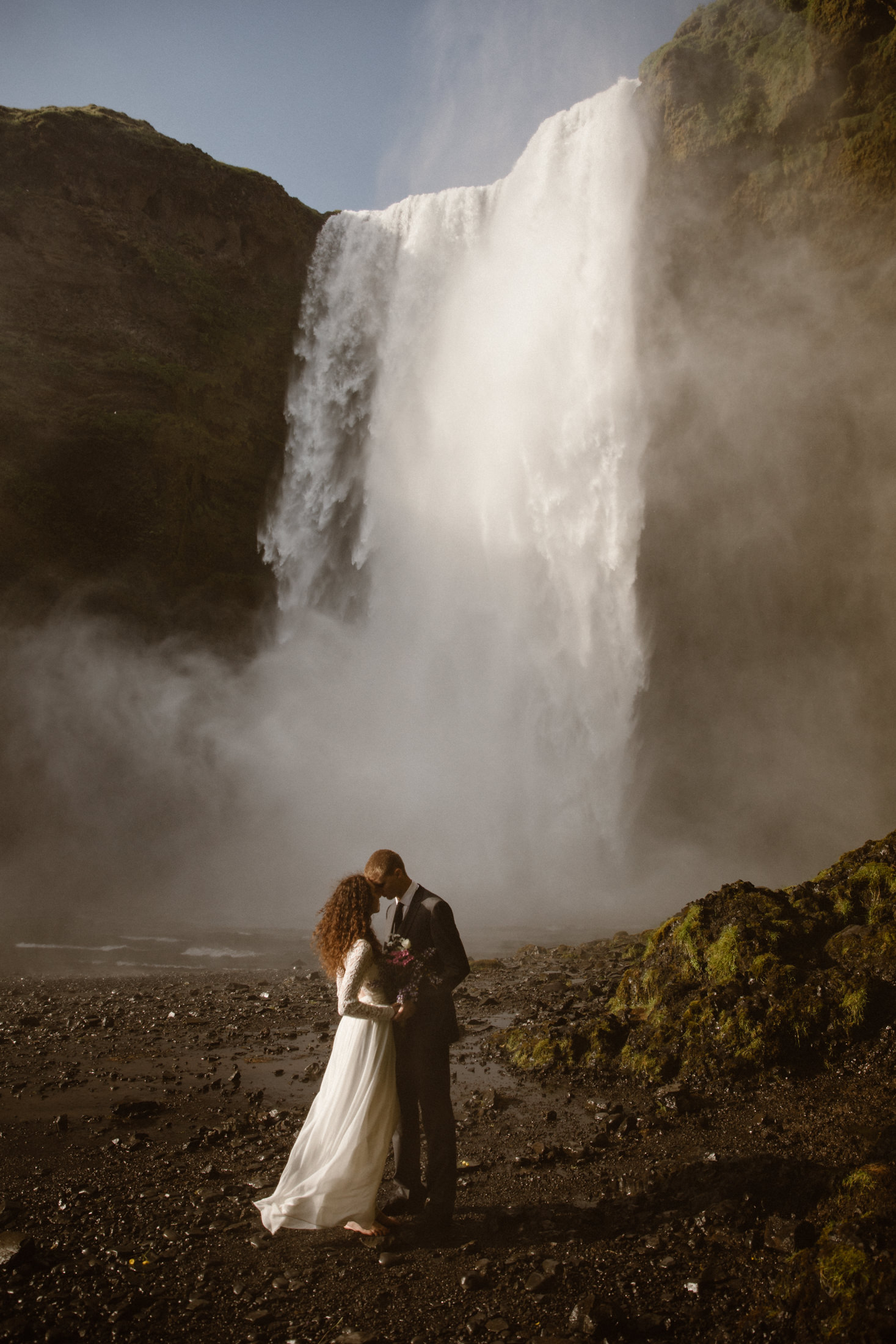 A couple decided to elope by a waterfall in Iceland for their wedding. Skogafoss Waterfall in Southern Iceland is the dreamiest place to get married.