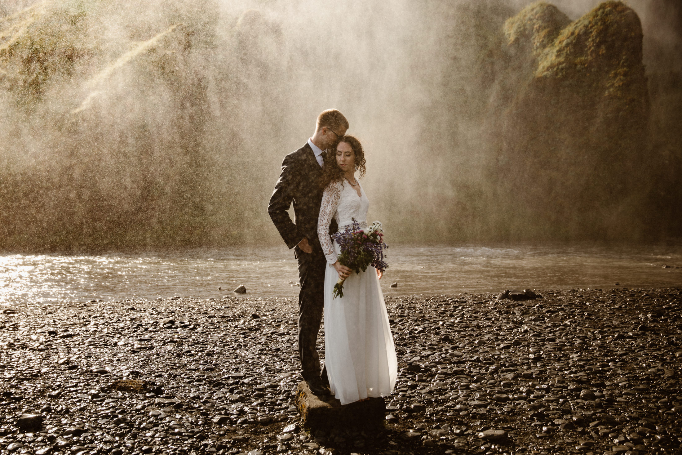 A couple has an intimate wedding in Iceland, just the two of them surrounded by moss covered volcanic rock and spray from the waterfall.