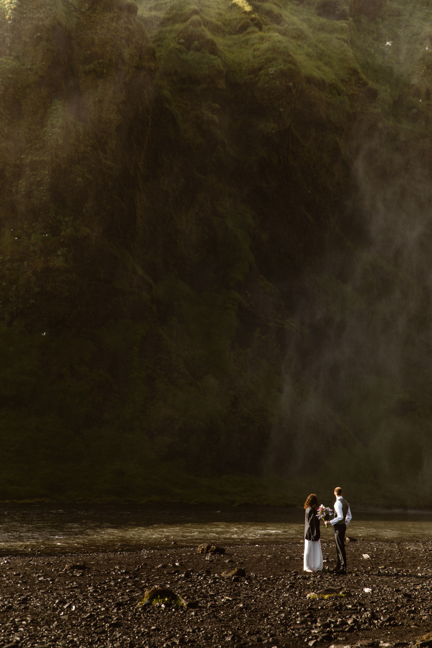 Eloping in Iceland by a waterfall a couple stands in awe at the moss covered cliffs in Iceland.