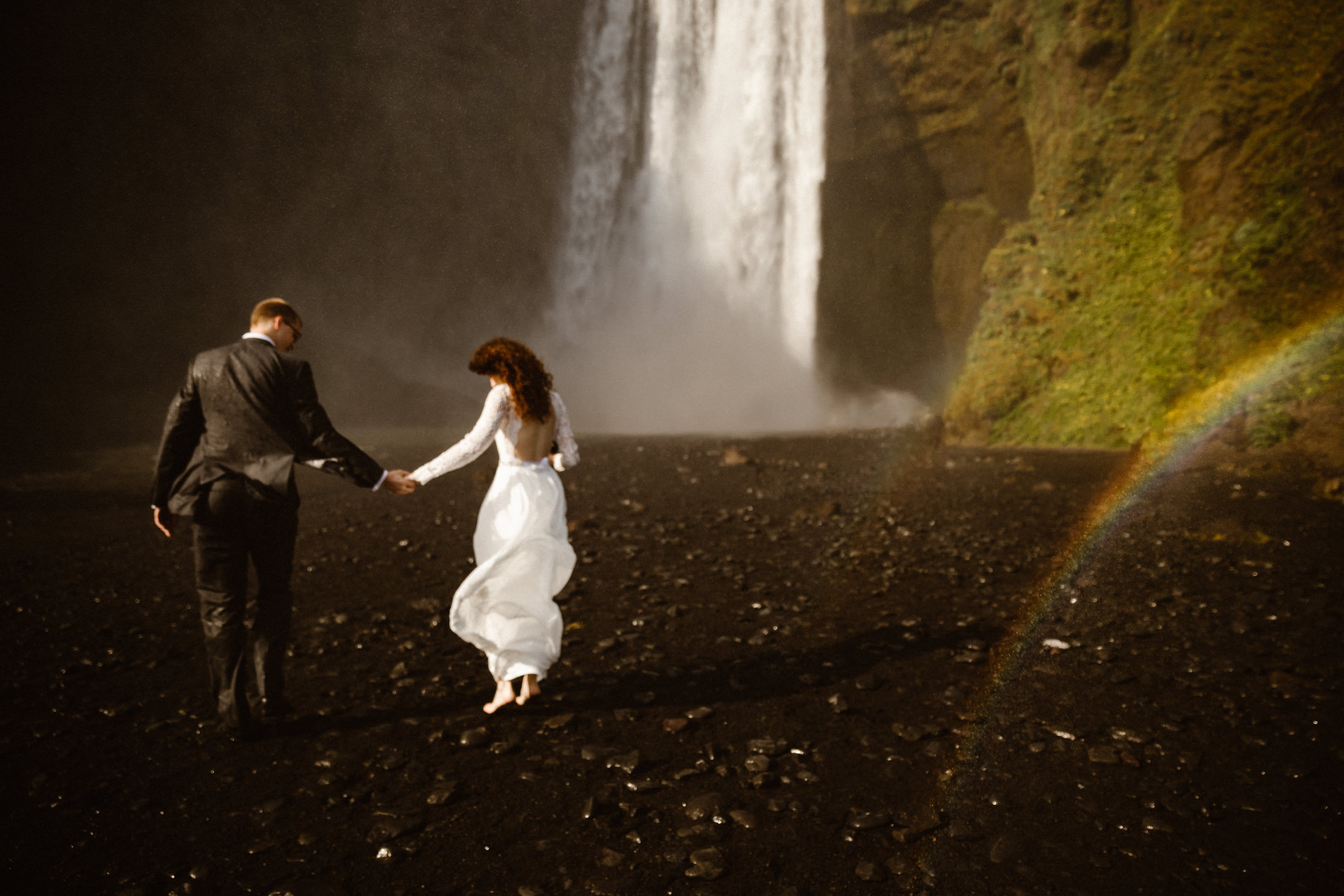 A couple walking towards a waterfall with a rainbow in Iceland.