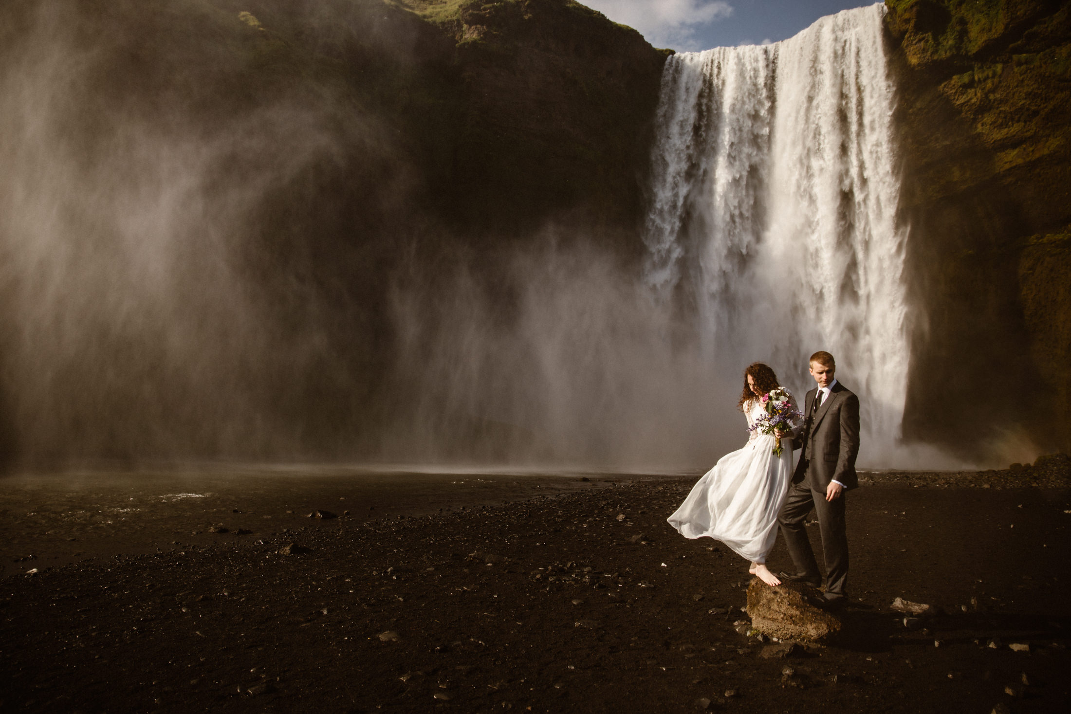 Couple standing on a rock in front of a waterfall in iceland.