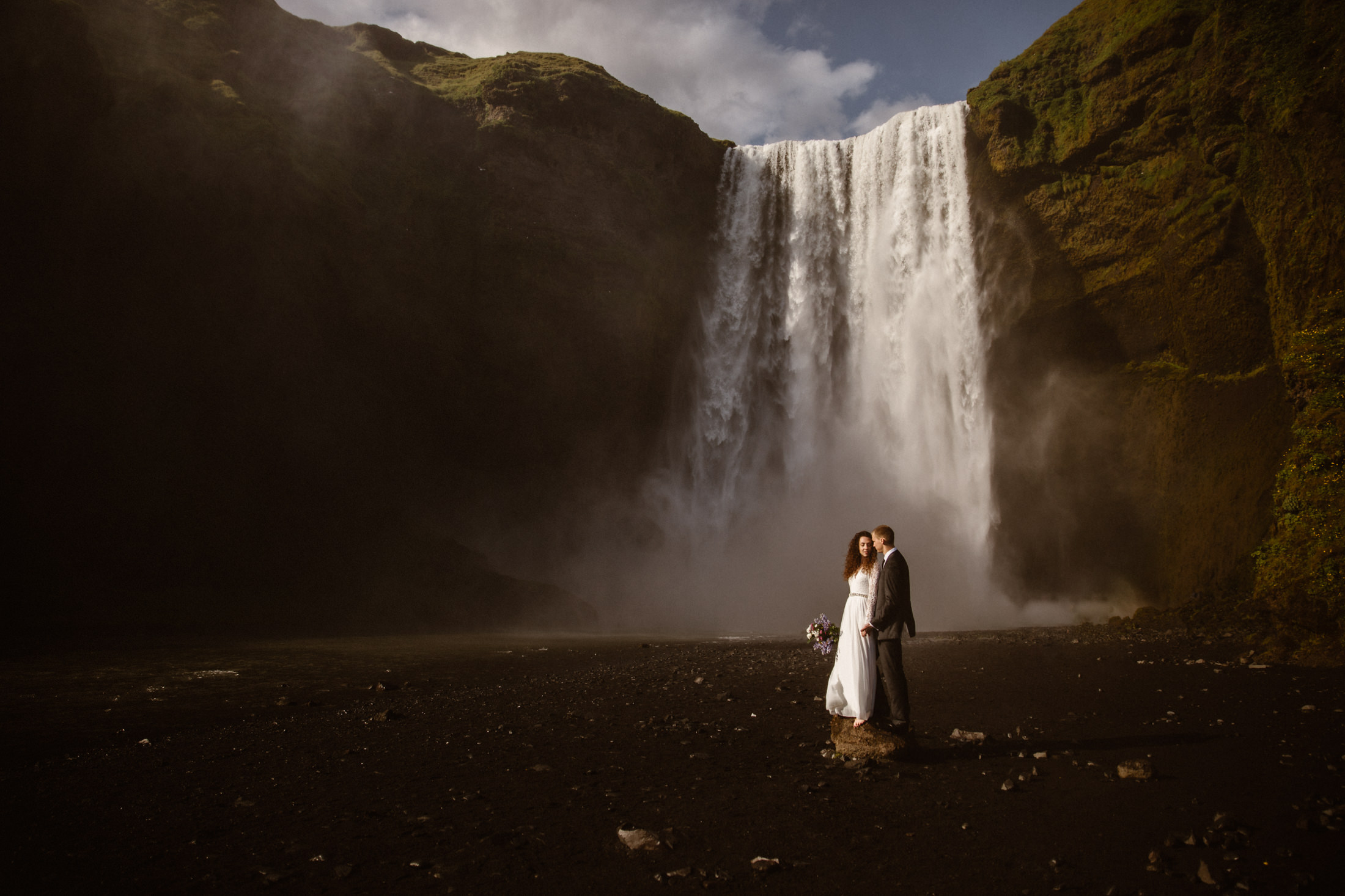A bride and groom stand in front of a raging waterfall in Iceland. Why elope in Iceland you might ask? So you can get married somewhere like this!