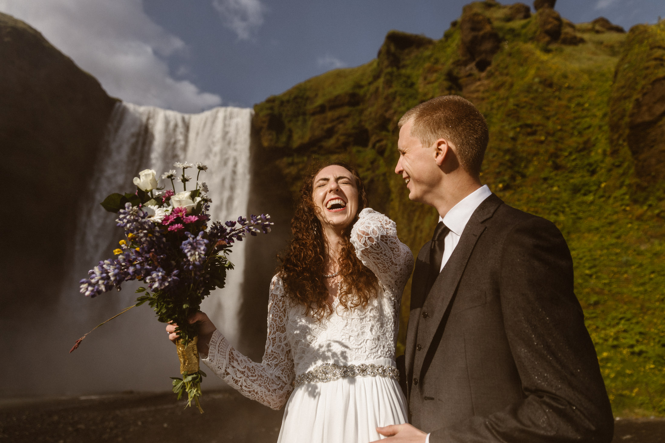 A bride and groom laugh as they stand in front of an Icelandic waterfall on their wedding day.