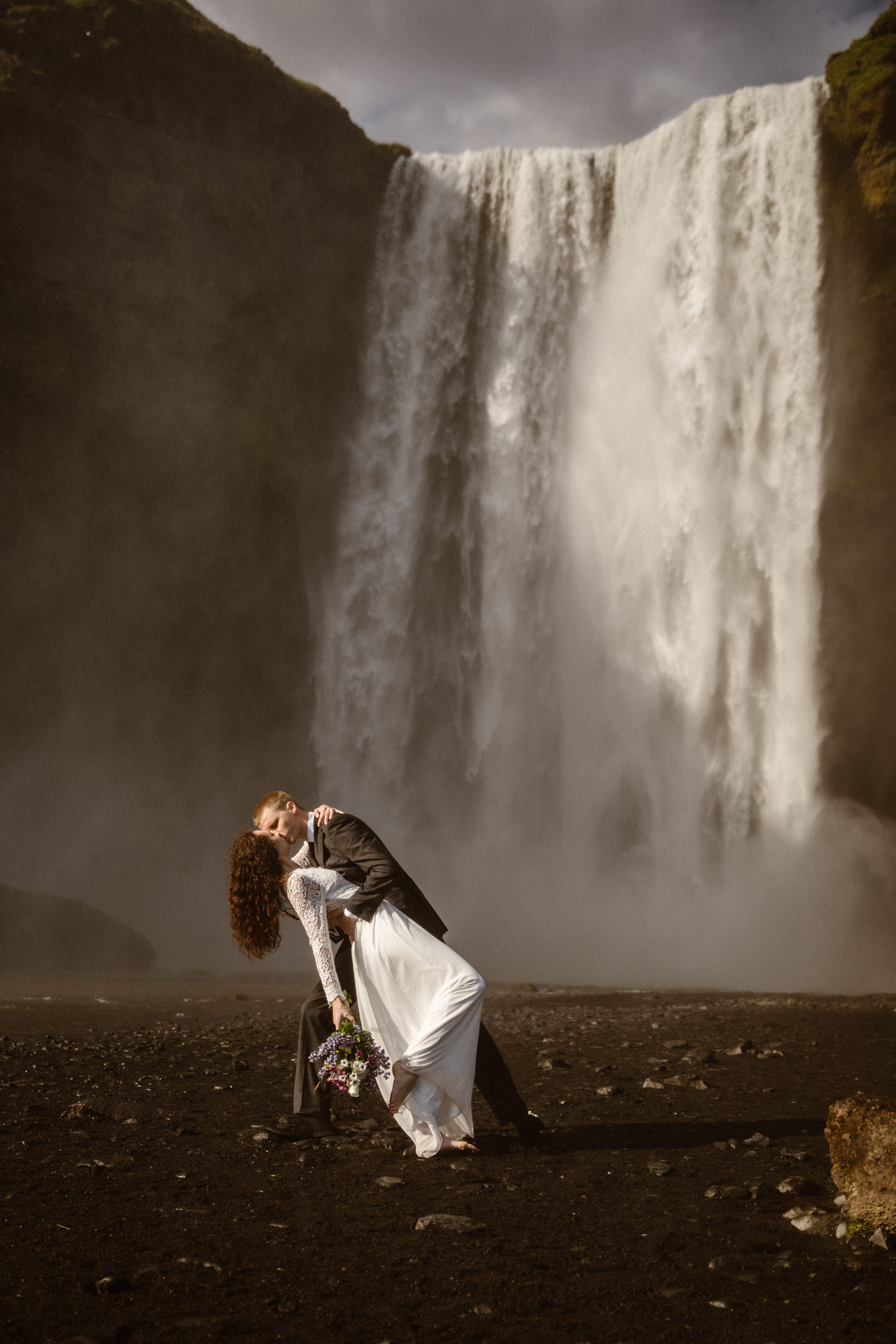 A couple kiss in front of a raging waterfall in Iceland. Surrounding by mist, rainbows and bird rooking in the high cliffs above. This is why Iceland is truly the best place to elope!