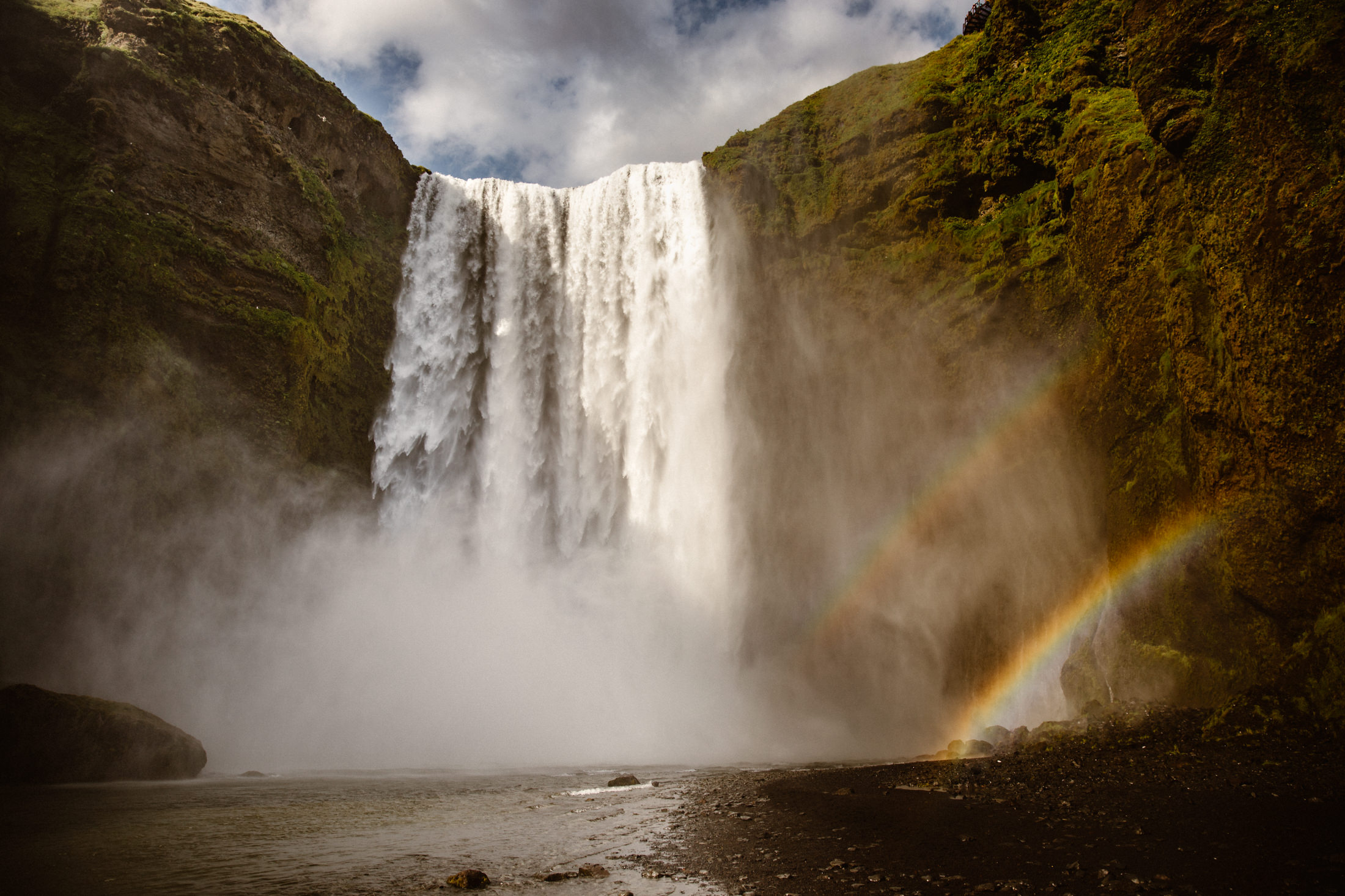 An epic waterfall in Southern Iceland with a double rainbow. A perfect place for your adventurous elopement wedding.