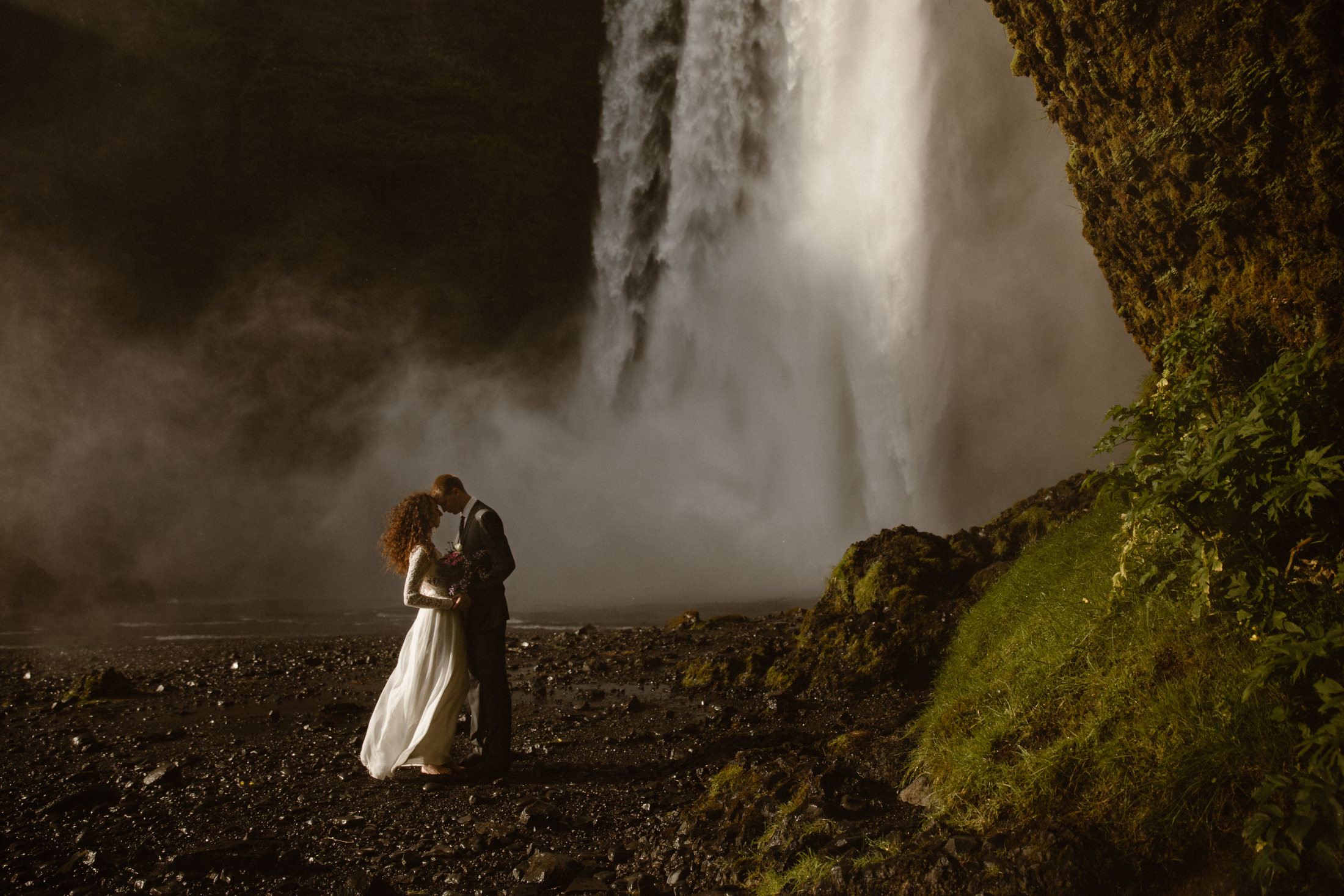 A bride and groom lean into each other under a large waterfall in Southern Iceland. They had an intimate wedding, just the two of them, at the base of a waterfall, surrounded by some of Iceland's most beautiful moss covered rocks and towering cliffs.