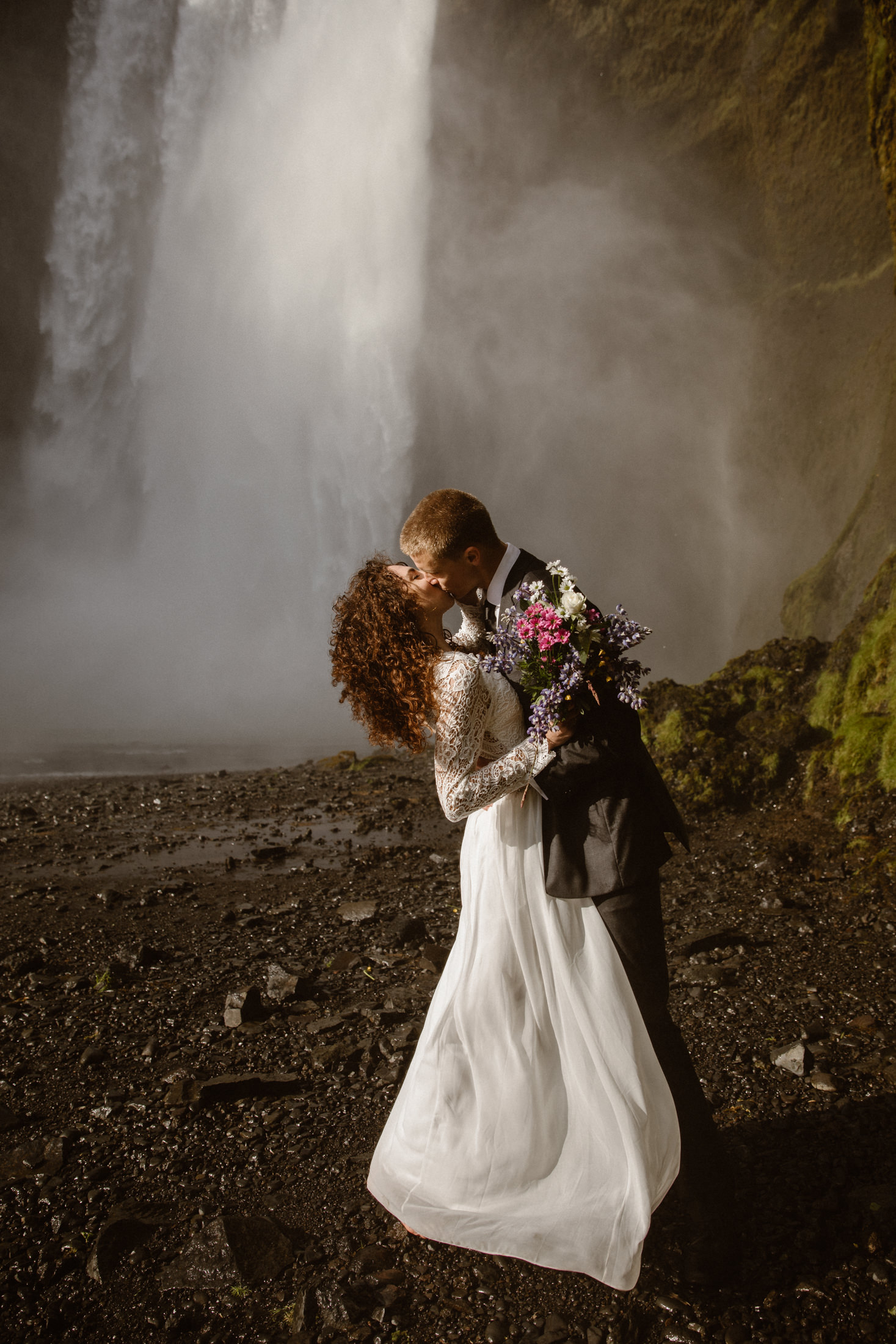 A bride and groom kiss at the base of a waterfall. Why should you elope in Iceland? Just imagine, being surrounded by volcanic rocks, mountains, glaciers, towering cliffs, black beaches and giant waterfalls!