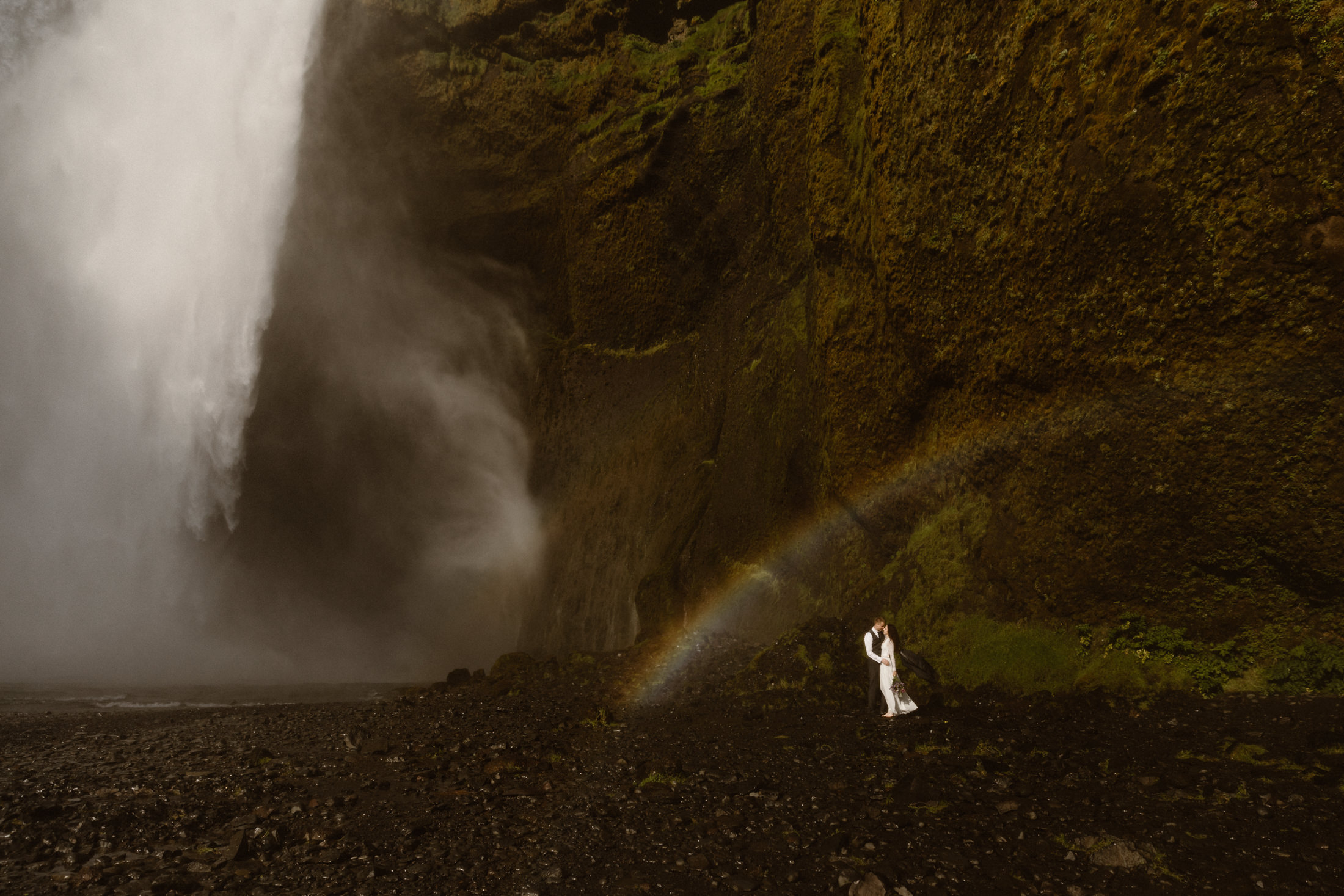 A couple embrace under a rainbow made by the mist of a large waterfall in Iceland's Southern coast. What a epic place to get married.