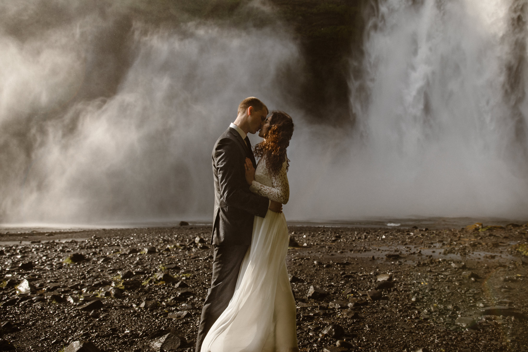 A couple kissing with the mist of Skogafoss waterfall in the background. Eloping in Iceland is perfect for adventurous couples.
