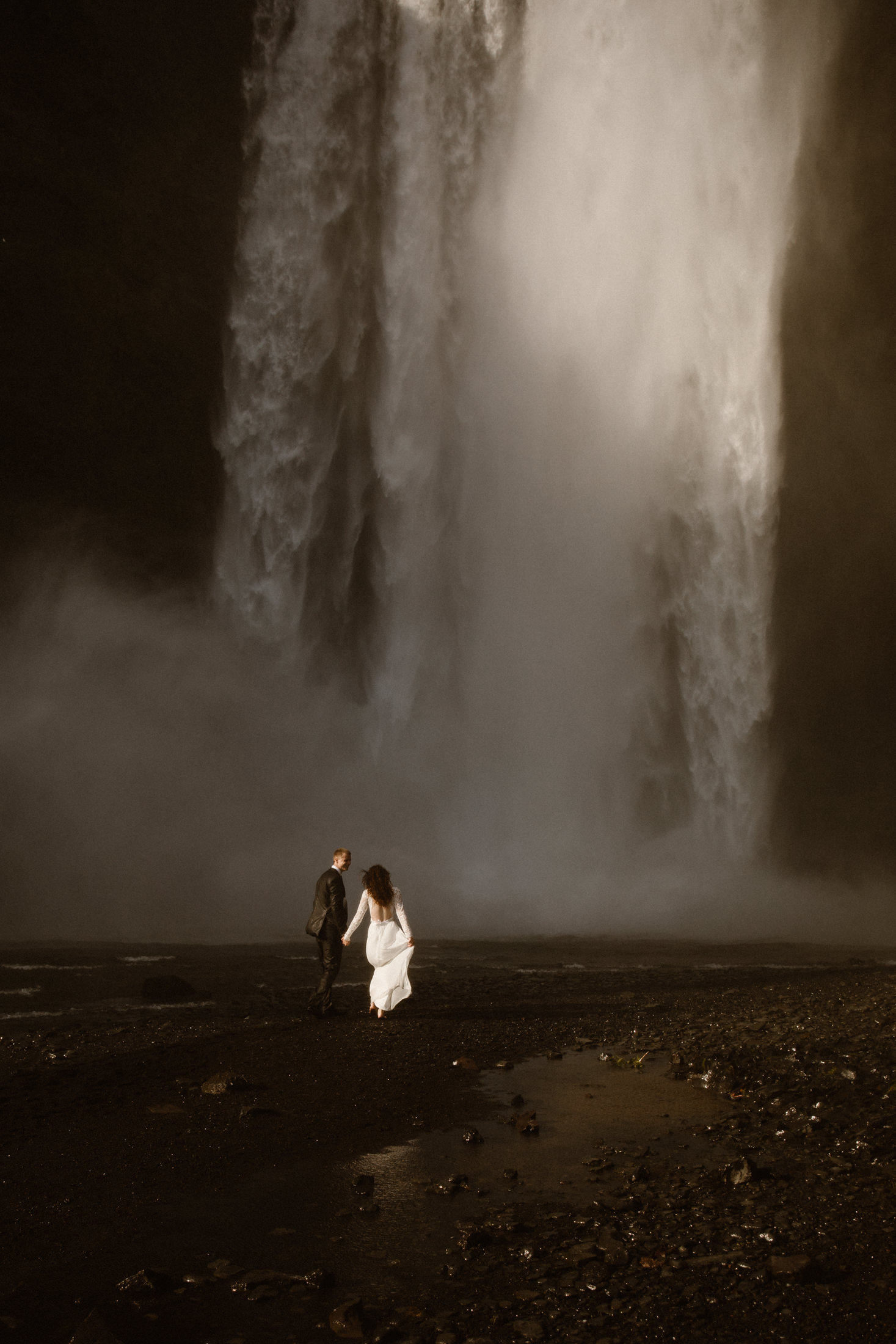 A bride and groom walk, hand in hand, in the dramatic Icelandic landscape towards one of the islands largest waterfalls. Just imagine what it would be like to get married here.