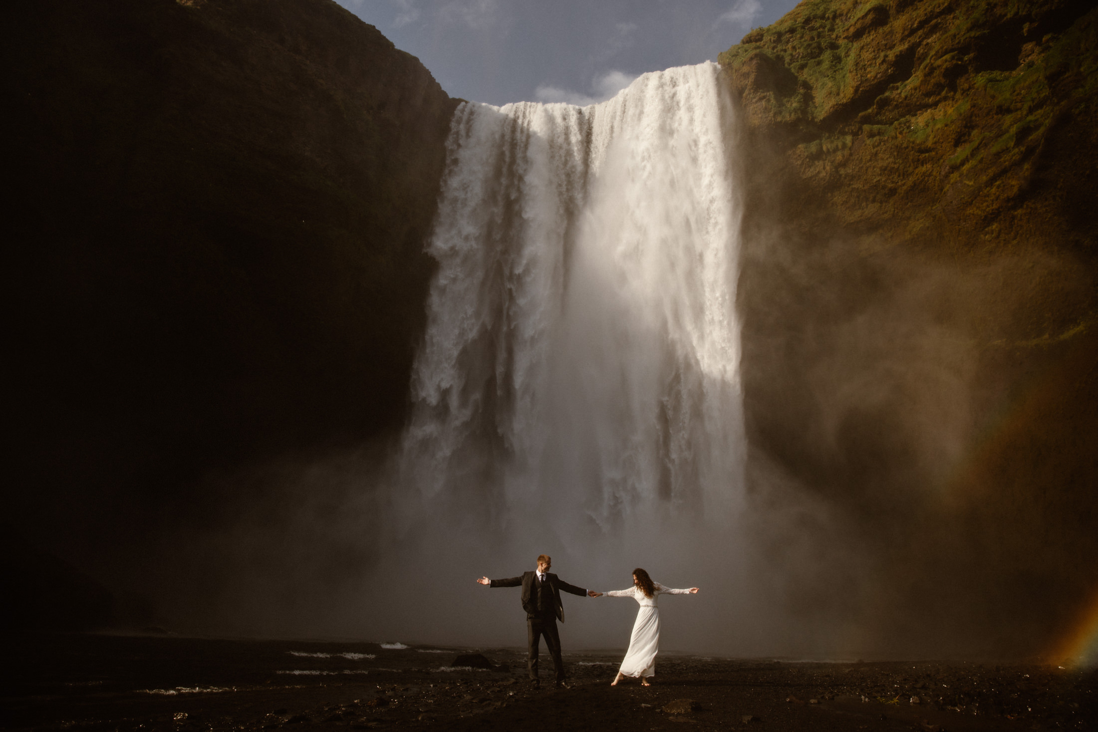 A couple celebrates their elopement in front of one of Iceland's biggest waterfalls. The dramatic landscape makes this the perfect place to elope!