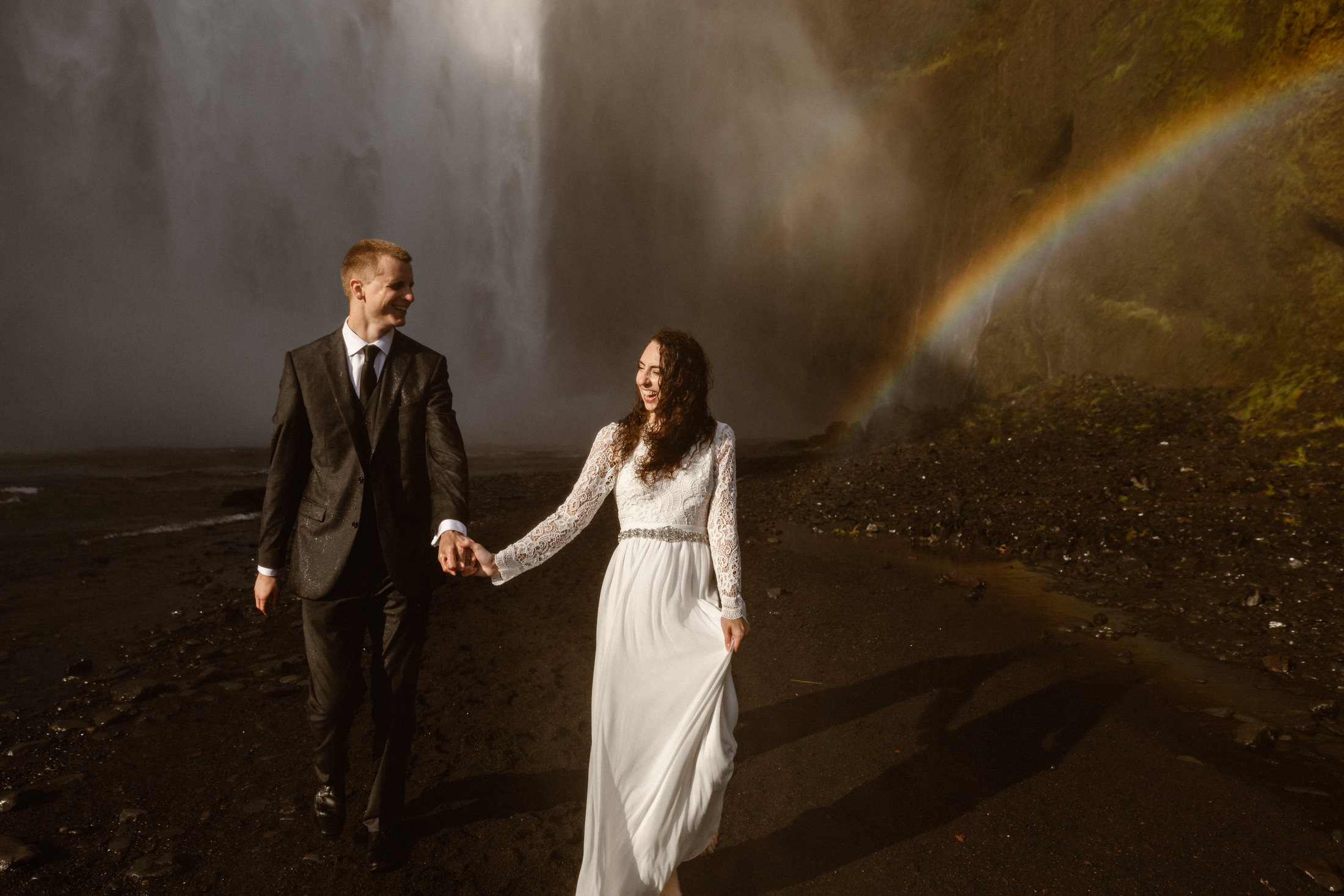A couple stands holding hands in front of a waterfall with a rainbow in the mist. Iceland's volcanic landscape makes it one of the best and most unique places to elope.