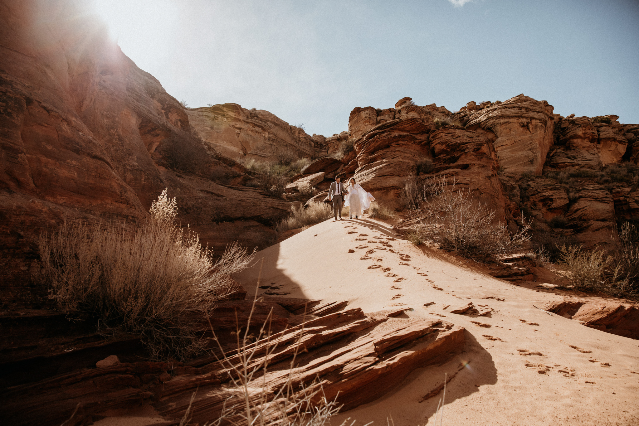 A bride and groom run down a large sand hill in Arizona. Having just eloped, hiking through a slot canyon was a perfect way to celebrate their marriage.