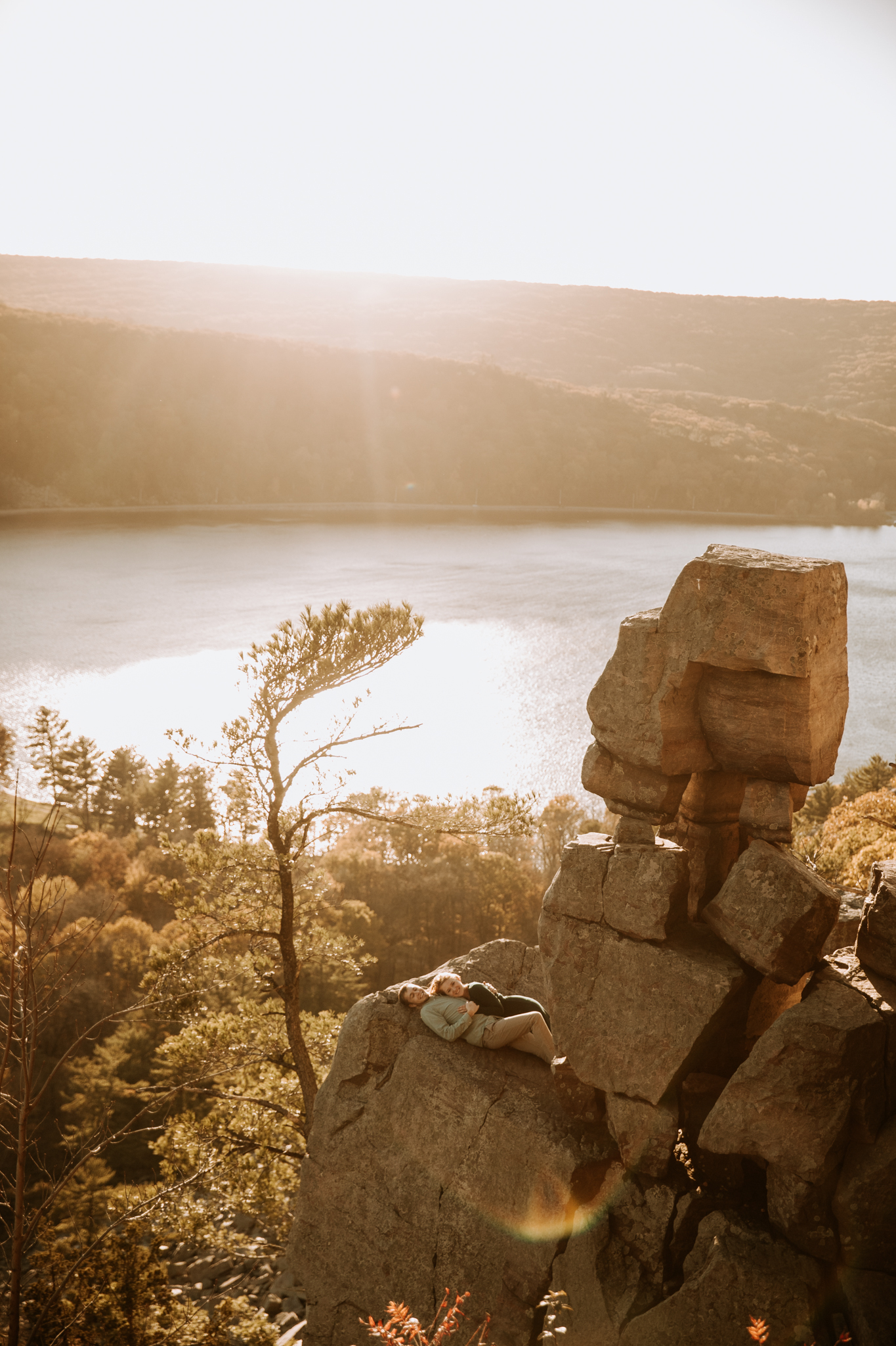 Couple lay on devils doorway rock face at sunset. An adventurous couple hiked up to the bluffs at Devil's Lake State Park in Wisconsin last fall for their engagement photos.