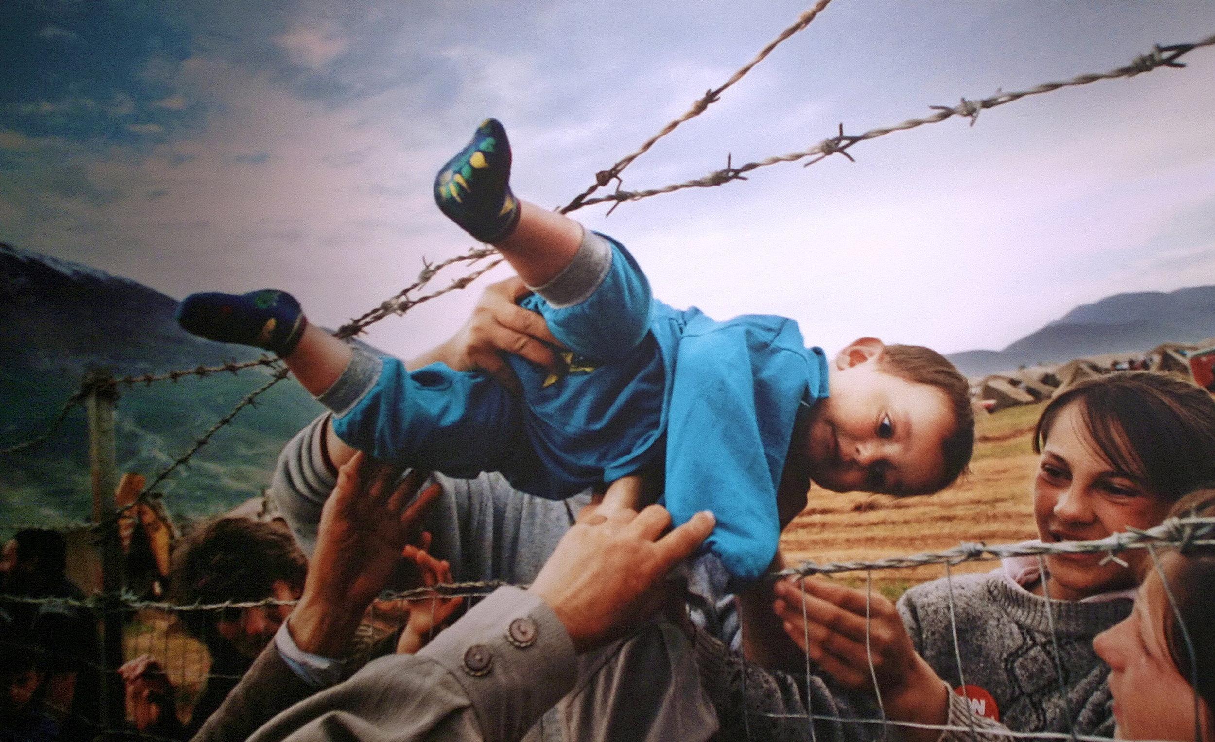 Refugees-Boy-Through-Fence.jpg