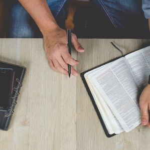 Table with Bible book and hand.jpg