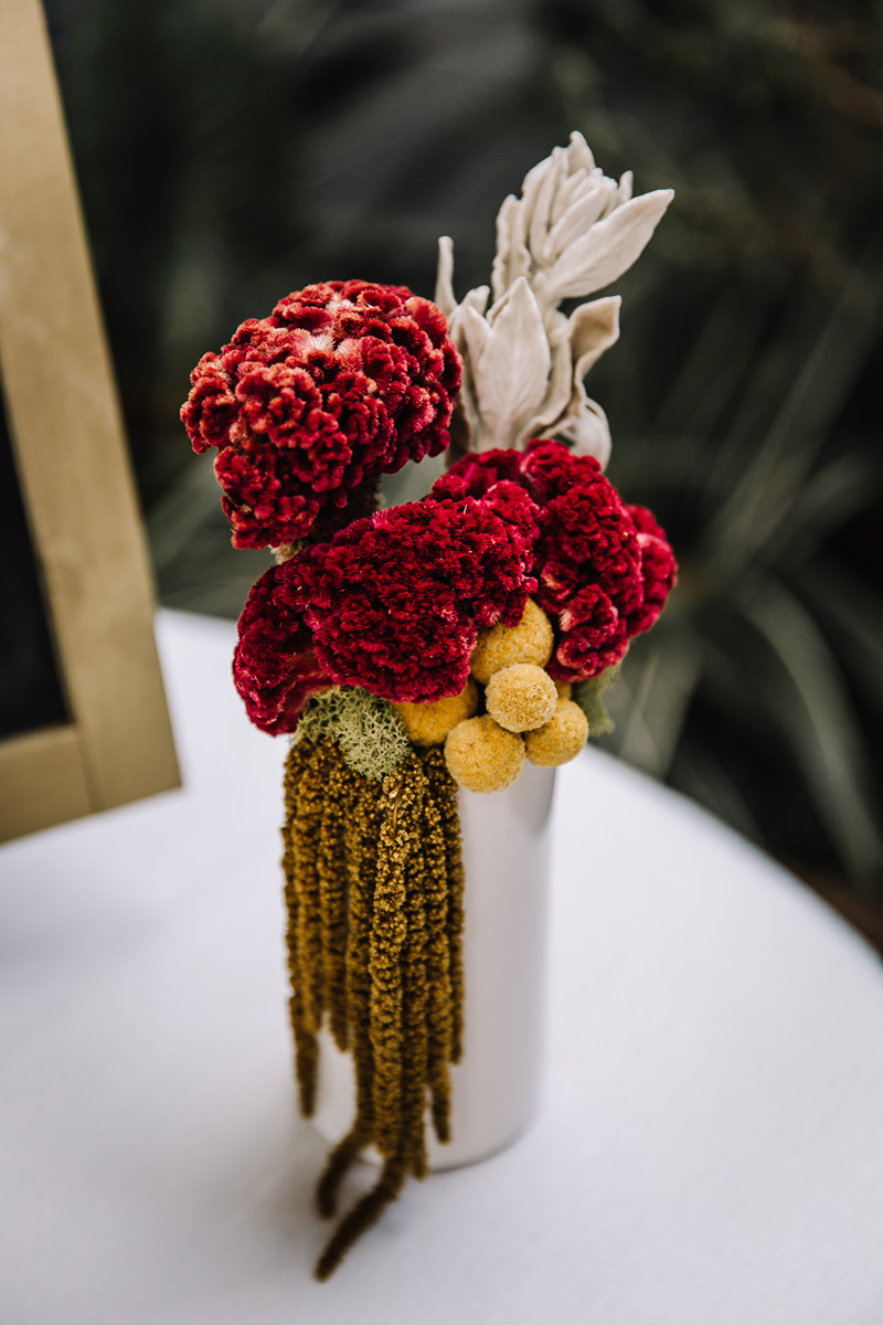 An elegant white budvase arrangement with rich red textured floral and moss hues.