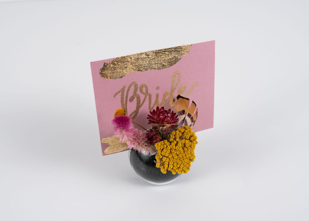 One of our globe place cards with a custom gold foiled name card. Filled with black sand and dried floral.