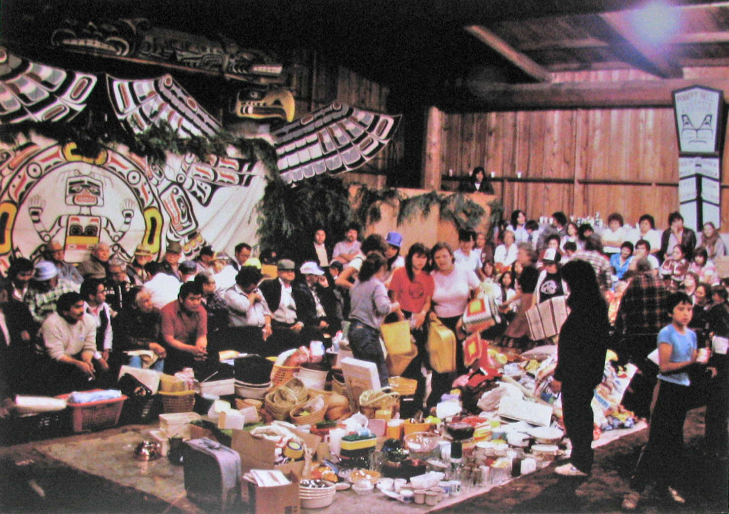 Gifts being distributed to guests at a potlatch given by Tlakwagila (W.T. Cranmer). Alert Bay, 1983.