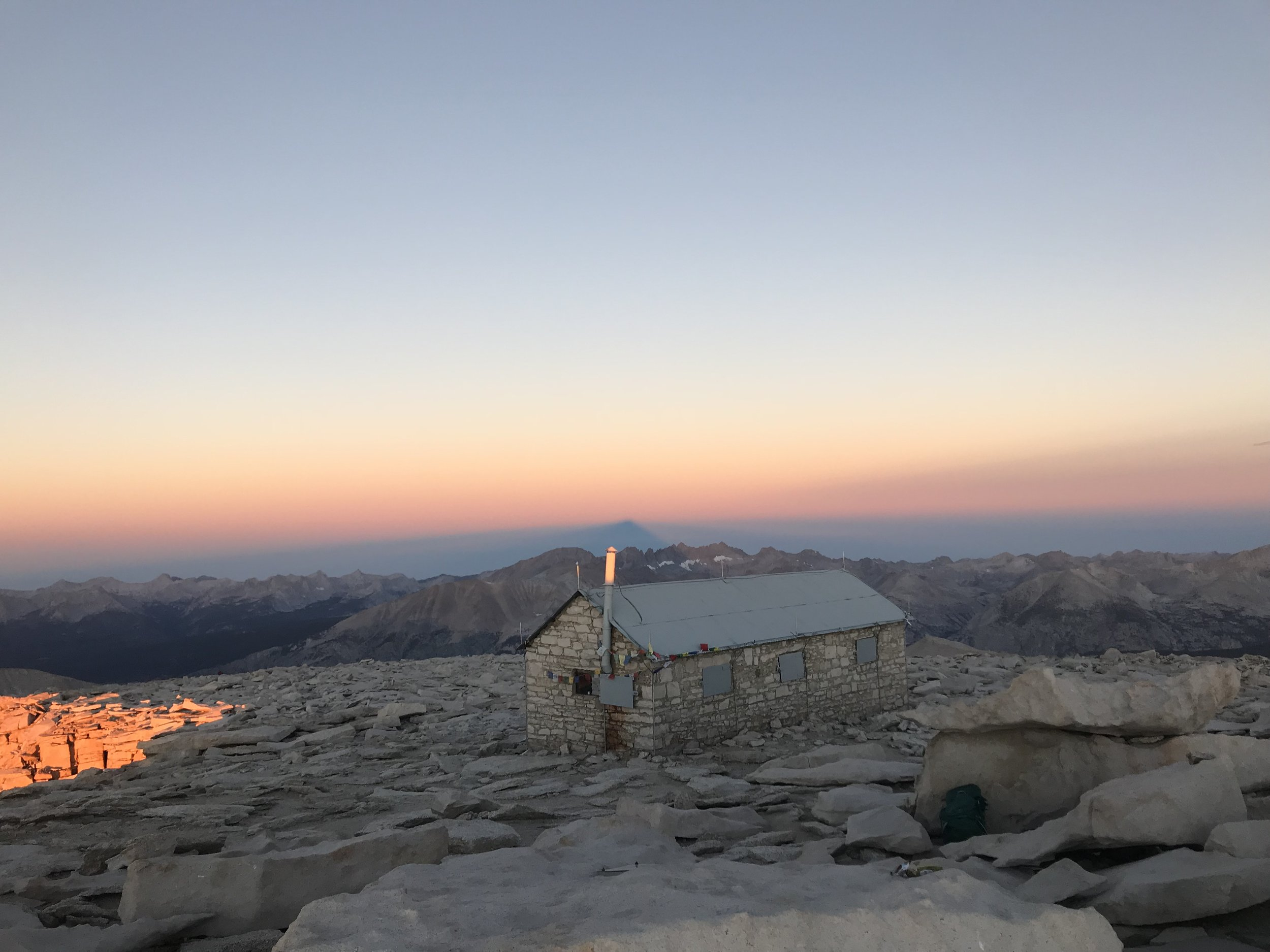 The small shelter atop Mt. Whitney, the shadow of the mountain looming into the horizon beyond.