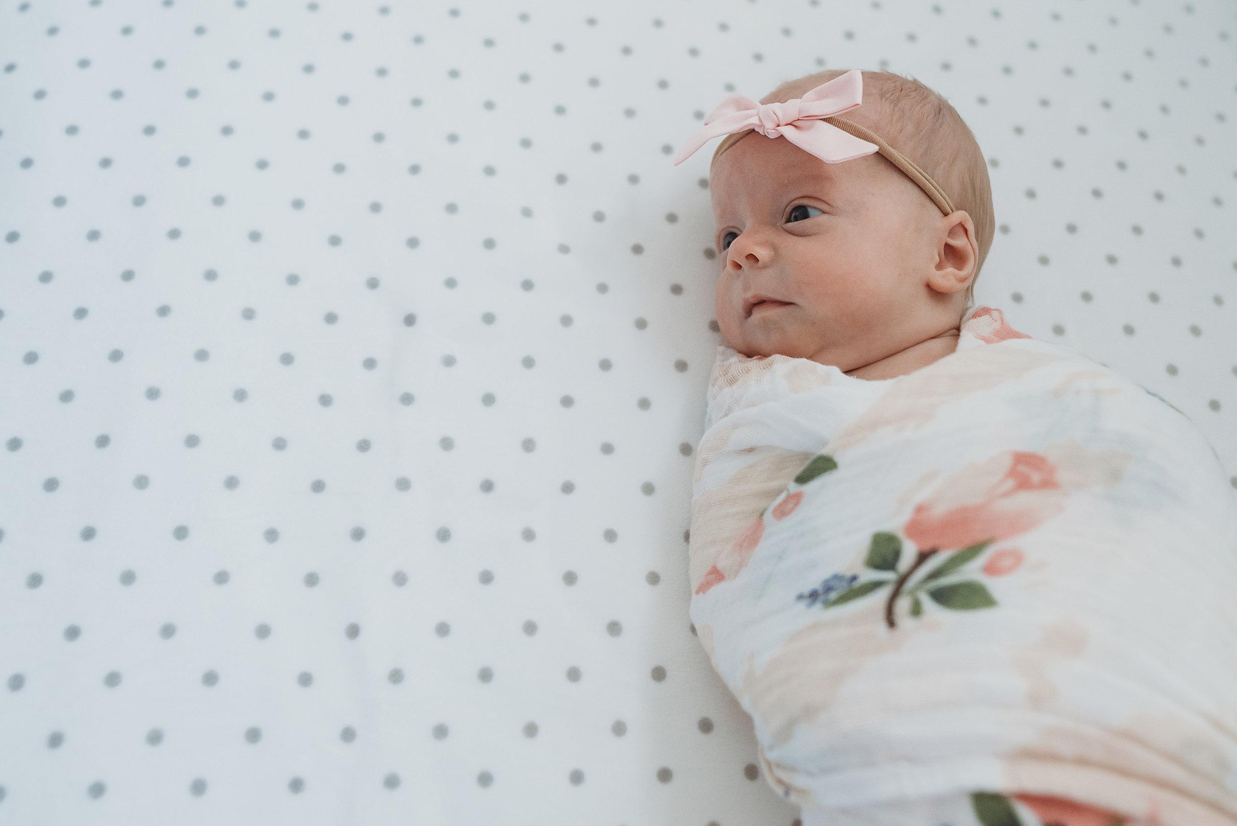 baby girl swaddled in crib