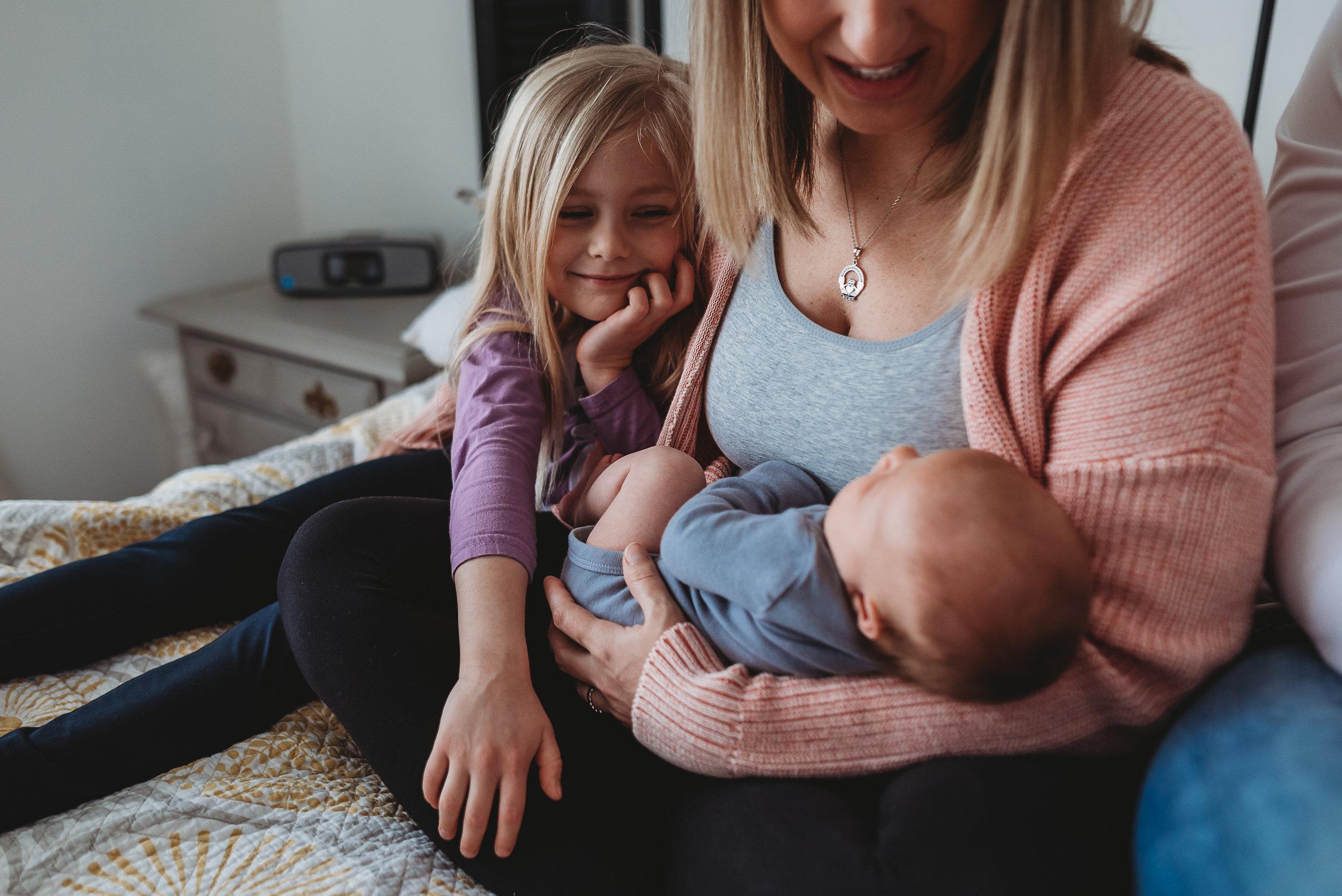 big sister looking at baby
