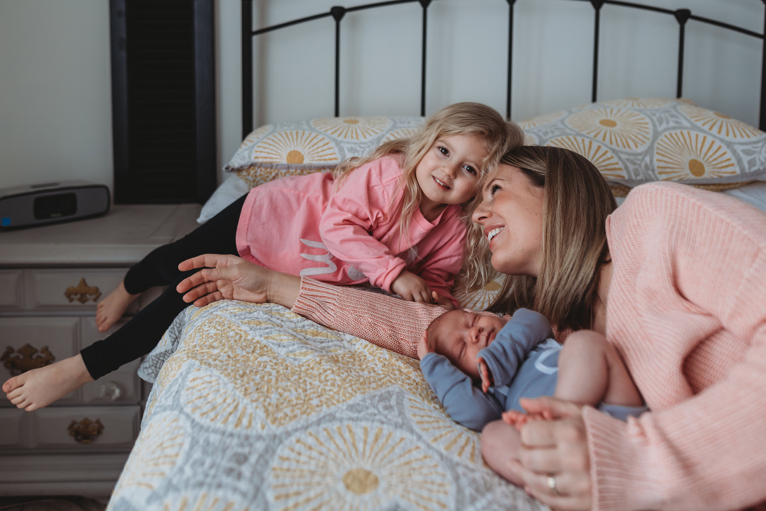 mom and two daughters on bed